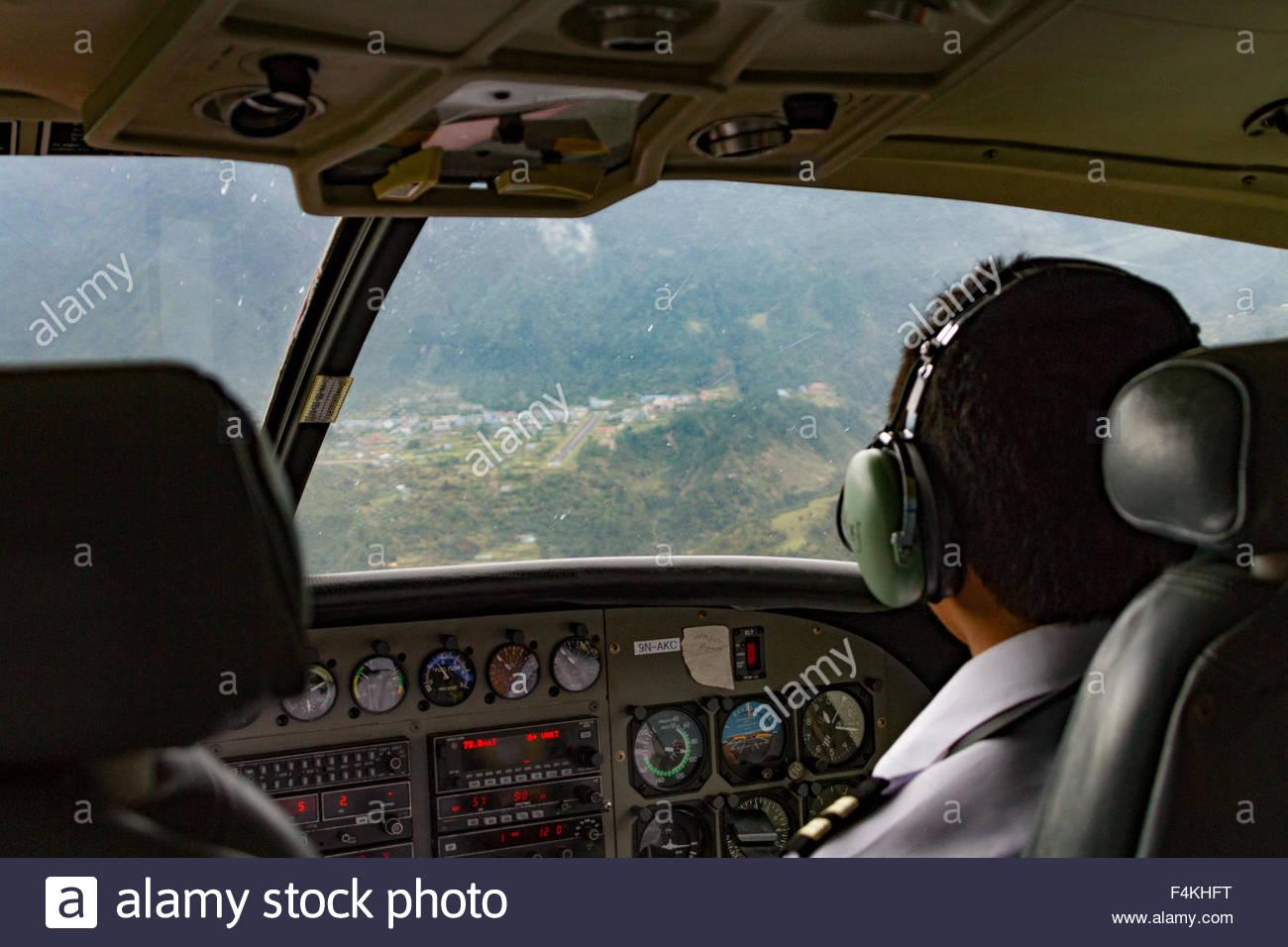 Il Cockpit vista guardando oltre il pilota della spalla sull approccio al Tenzing-Hillary (Lukla) Aeroporto in Nepal Immagini Stock