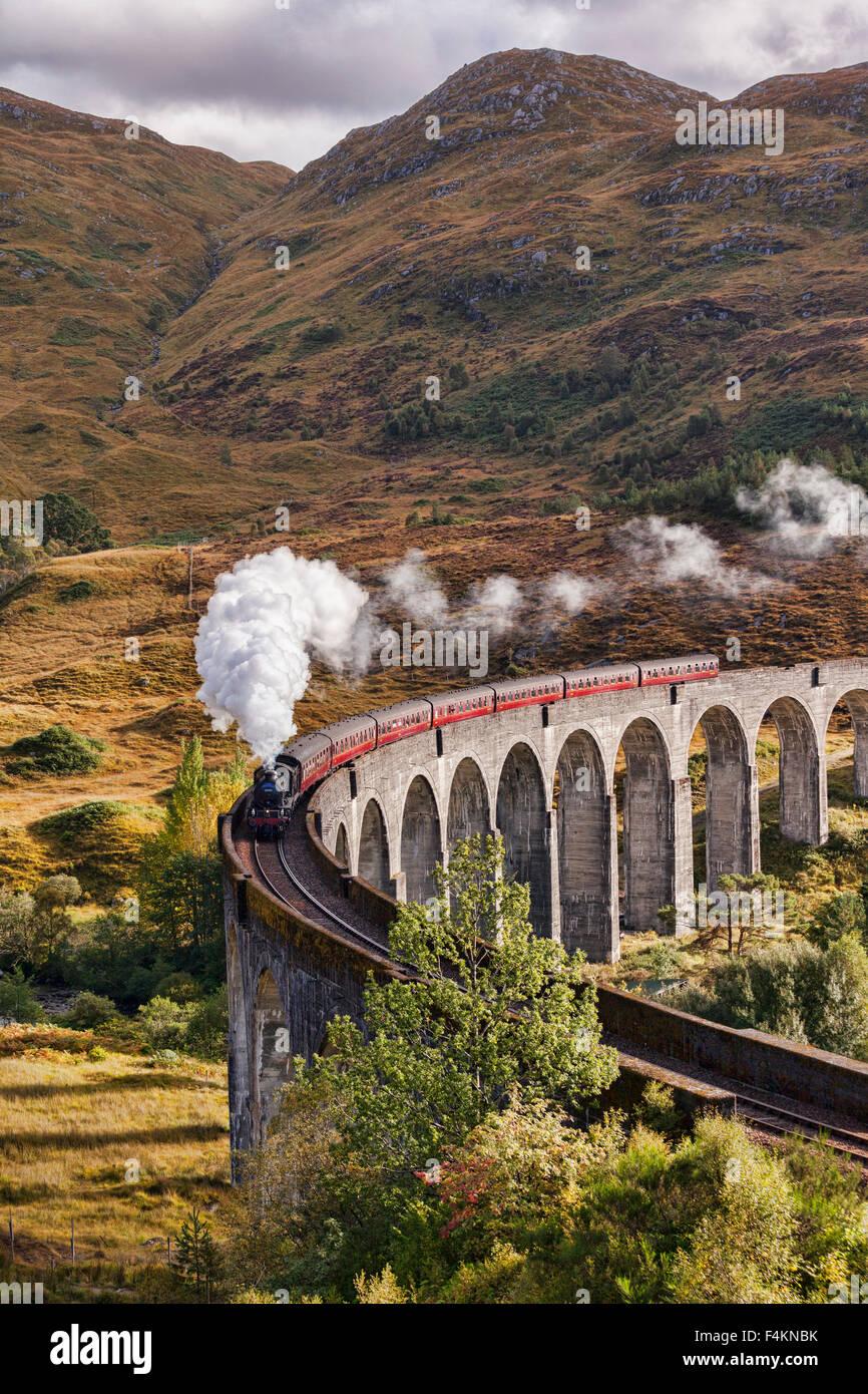 Il Giacobita treno a vapore che insuffla vapore dallo scarico come si attraversa il viadotto Glenfinnan, Highland, Immagini Stock