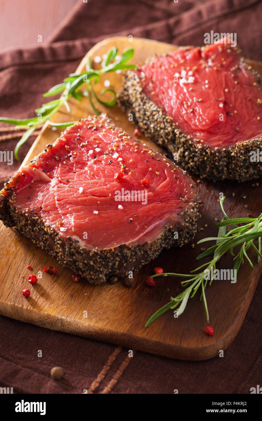 Raw bistecca di manzo con spezie e rosmarino su sfondo di legno Immagini Stock