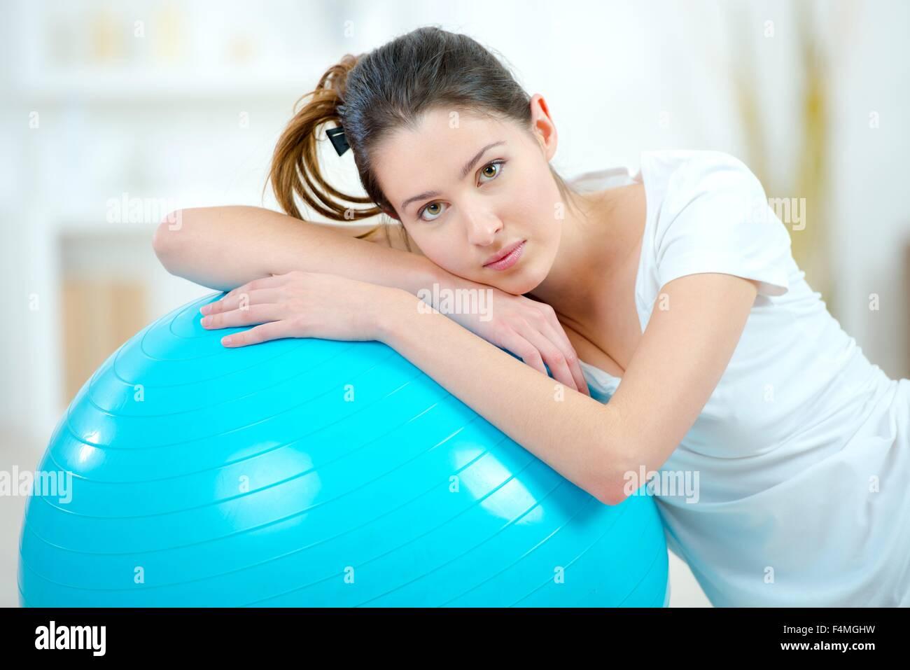 Ragazza appoggiata sulla sfera di aerobica Immagini Stock