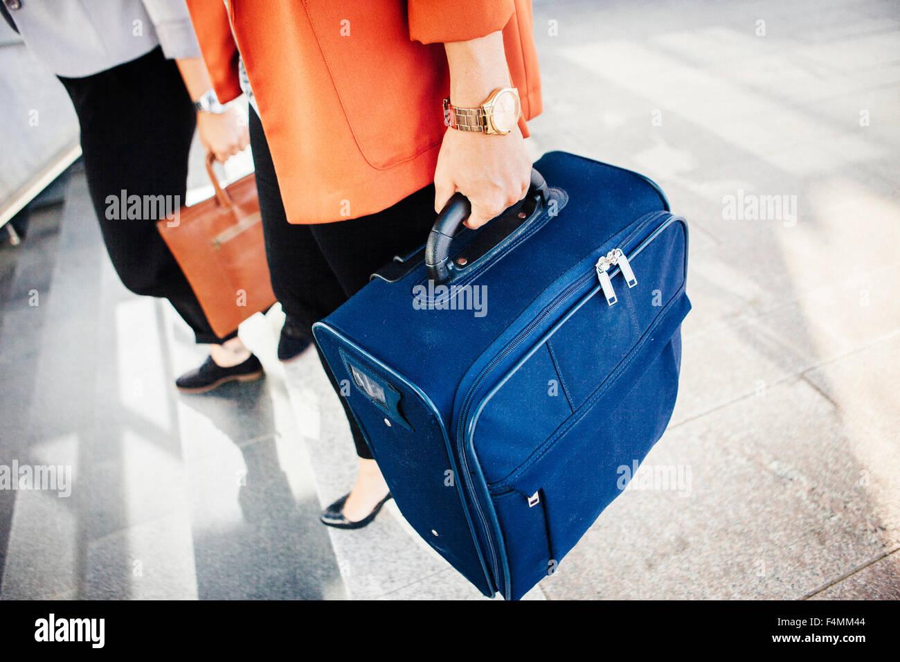 Sezione bassa di imprenditrici con bagagli si sta spostando verso il basso le fasi della stazione ferroviaria Immagini Stock