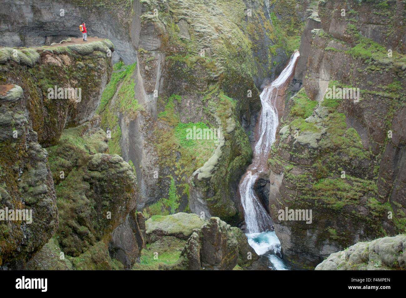 Persona sopraffatte da una cascata nel Canyon Fjadrargljufur, Sudhurland, Islanda. Immagini Stock