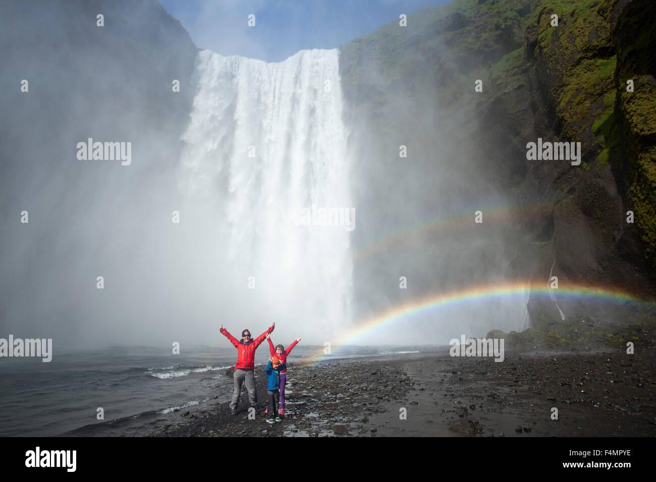 La famiglia in rainbow sotto 60m-alta cascata Skogafoss, Skogar, Sudhurland, Islanda. Immagini Stock