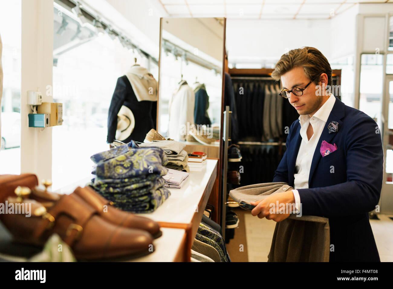 Addetto alle vendite guardando t-shirt in negozio di abbigliamento Immagini  Stock 5ab21e4ee82