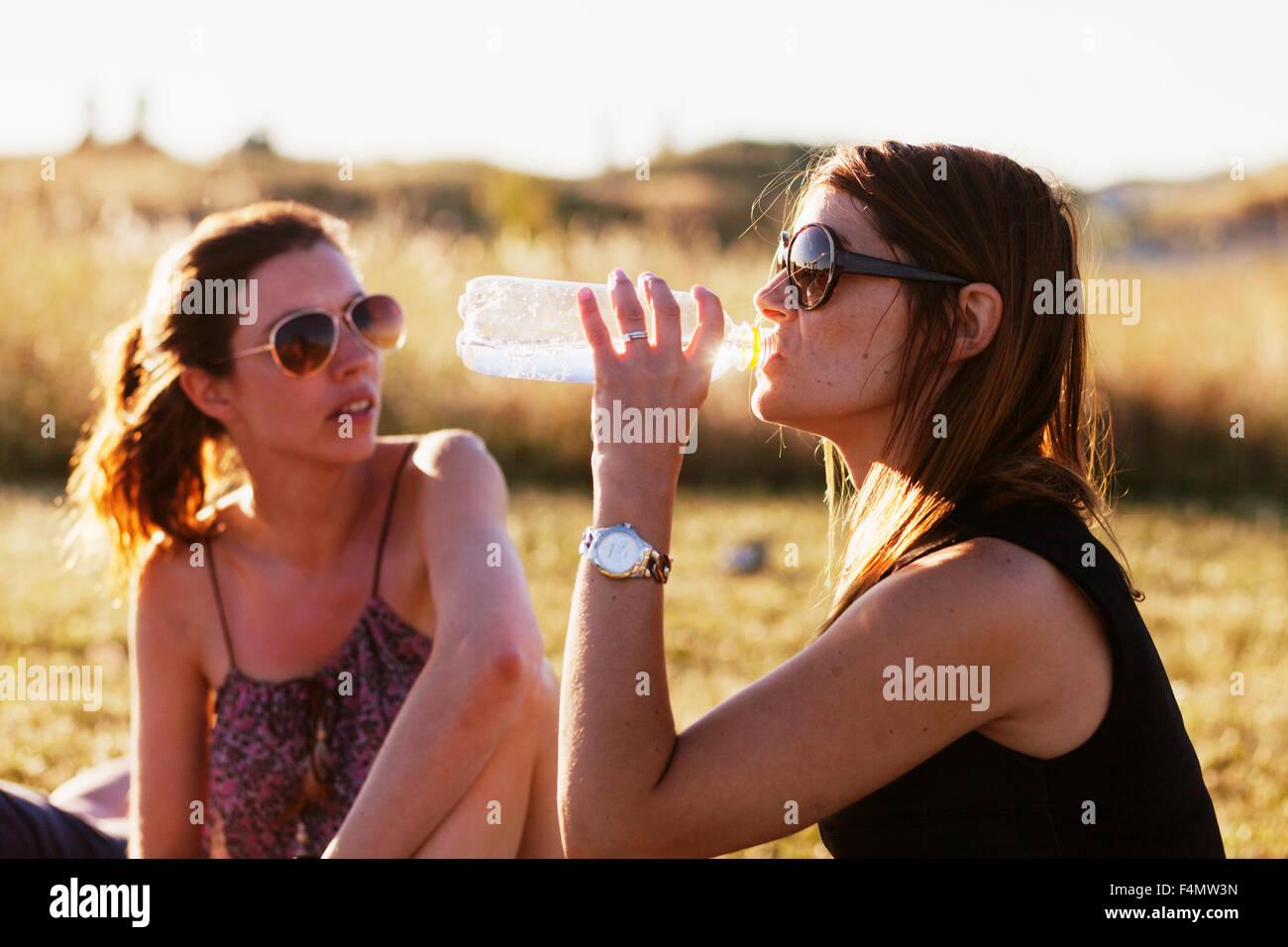 Donna seduta da amico e acqua potabile sul campo Immagini Stock