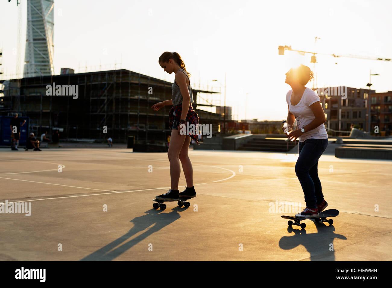 A lunghezza piena di adolescenti amici skateboarding in skate park Immagini Stock