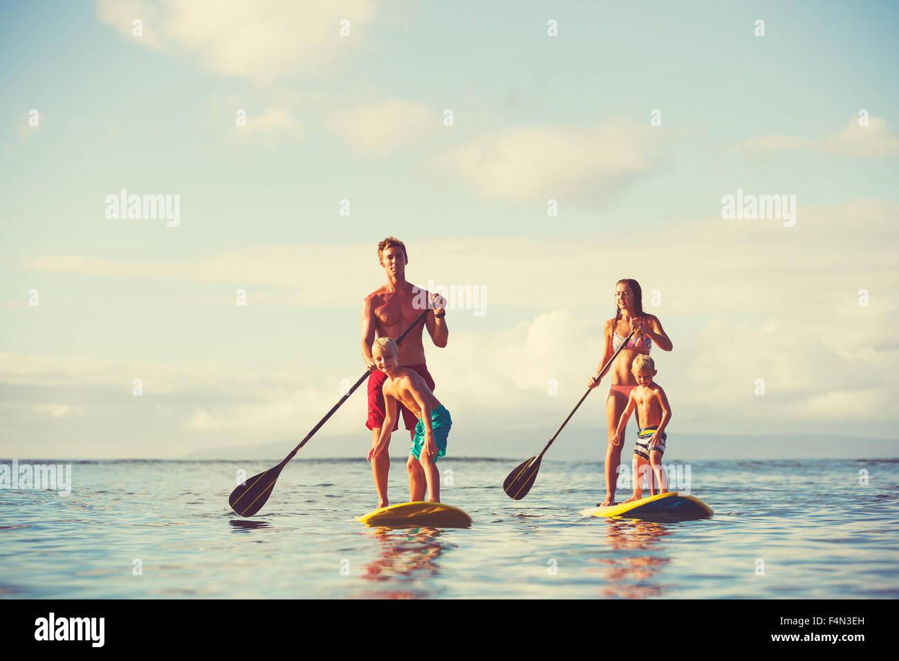 Famiglia stand up paddling presso sunrise, estate divertimento outdoor lifestyle Immagini Stock