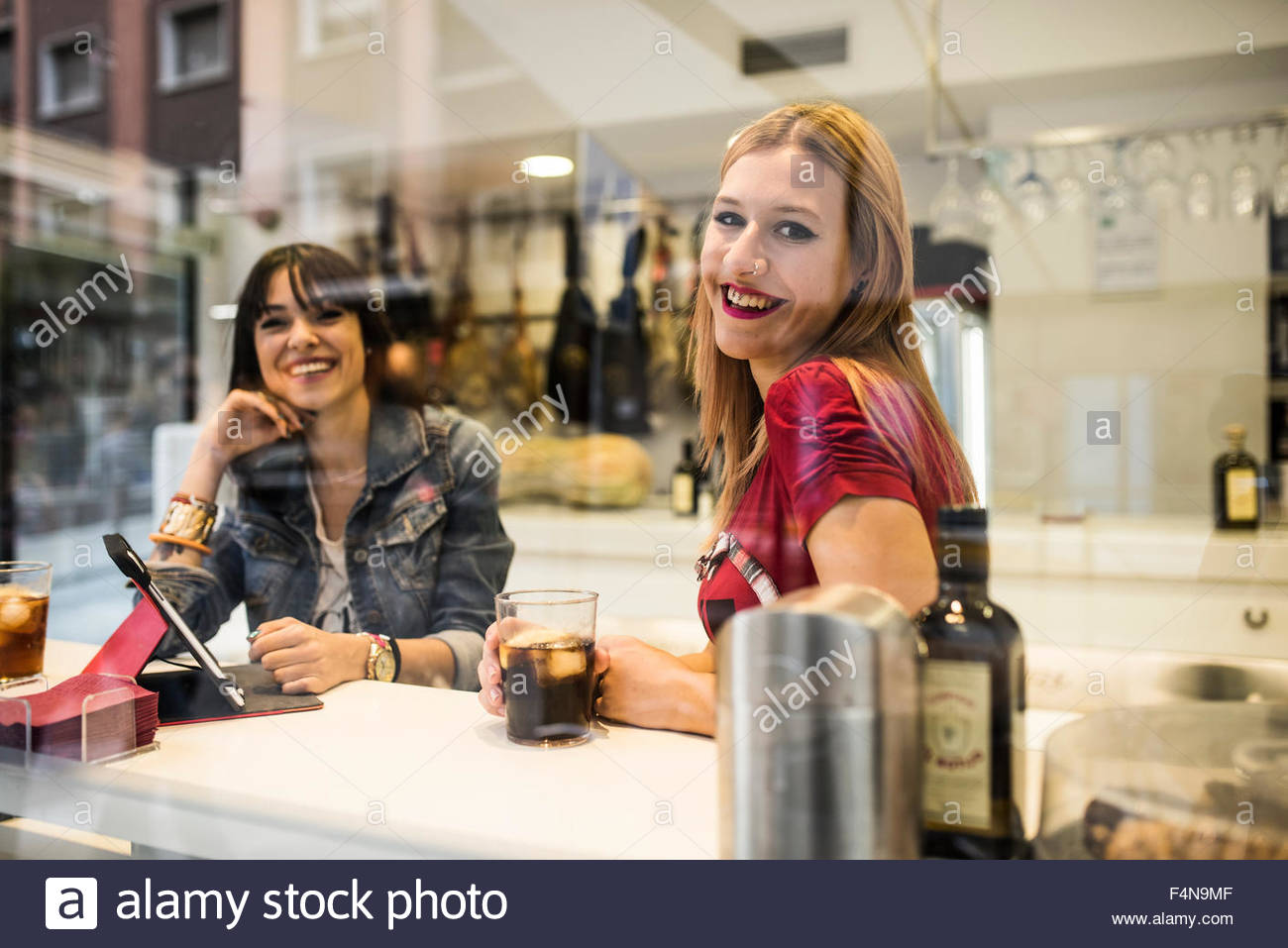 Felice di due giovani donne in un bar con bevande e tavoletta digitale Immagini Stock