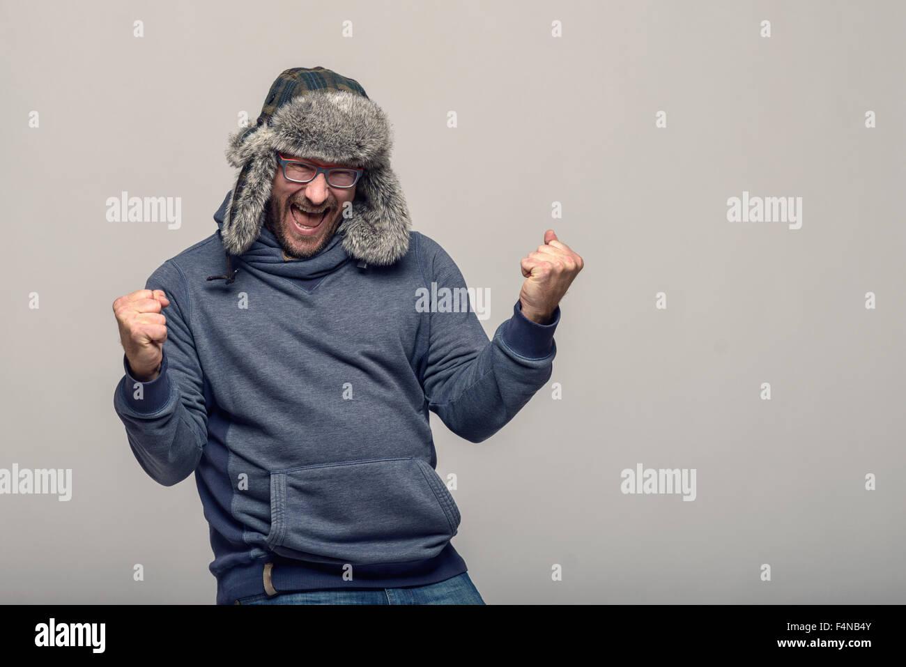 Felice l'uomo con gli occhiali e un cappello invernale il tifo e celebra il suo sollevamento rinserrata pugni in aria con un esultante expre Foto Stock