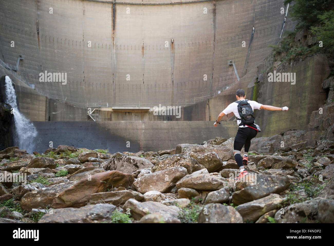 Ultra-trail runner saltando sulle rocce di un fiume in natura Immagini Stock