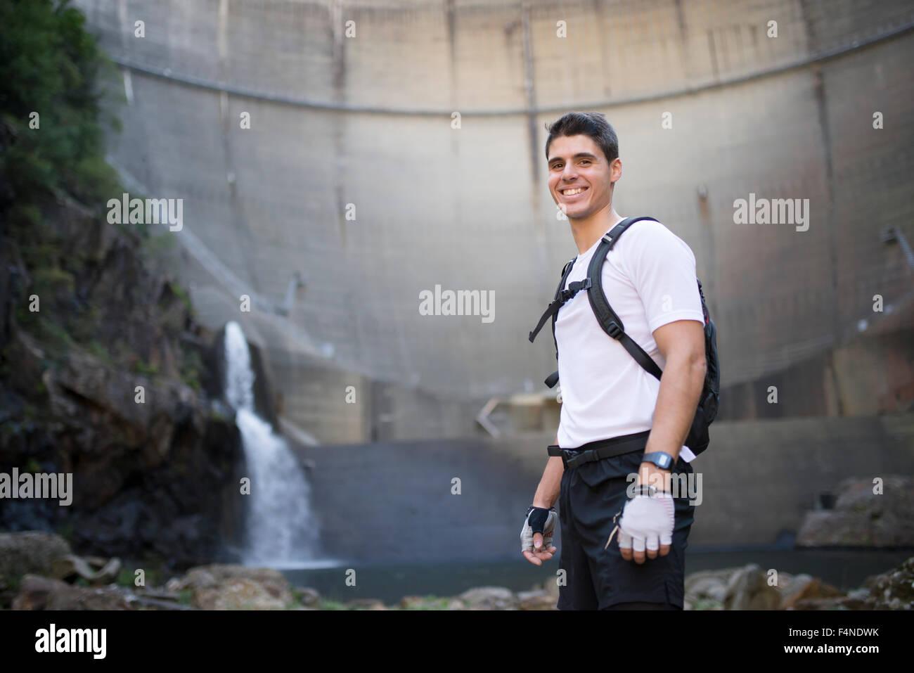 Sorridente ultra-trail runner con una diga in background Immagini Stock