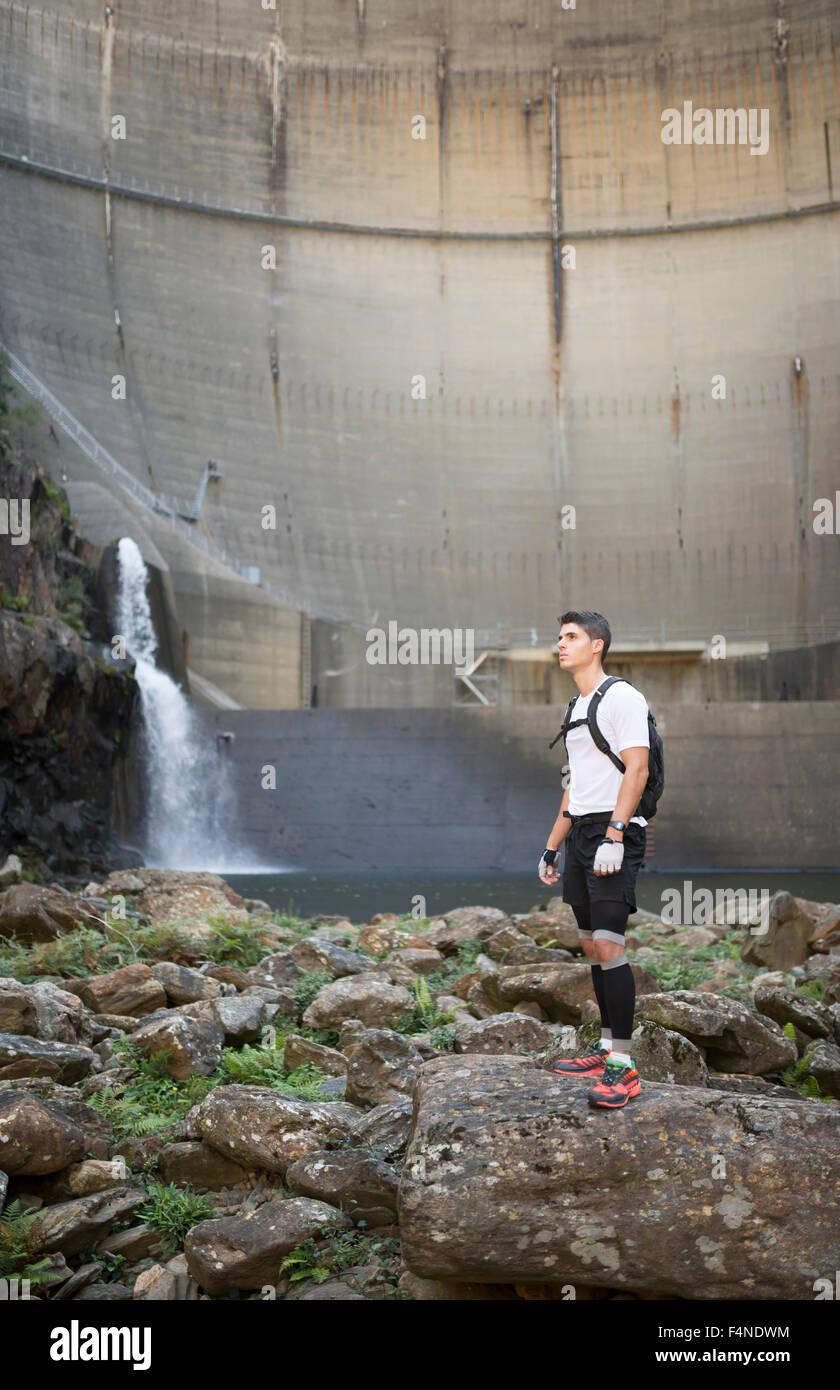 Ultra-trail runner con una diga in background Immagini Stock