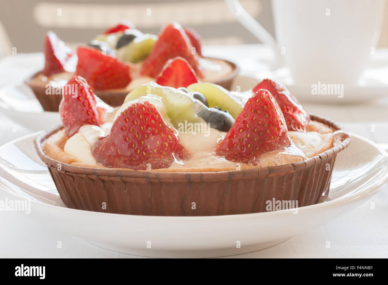 Crostate di frutta fatta riempito con crema di fragole patissiere kiwi e mirtilli Immagini Stock