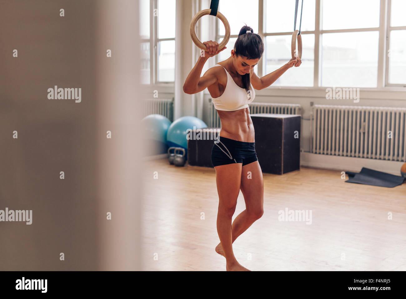 Donna muscolare rilassante dopo allenamento in palestra. Donna Fitness tenendo break da immersione esercizio. Crossfit Immagini Stock