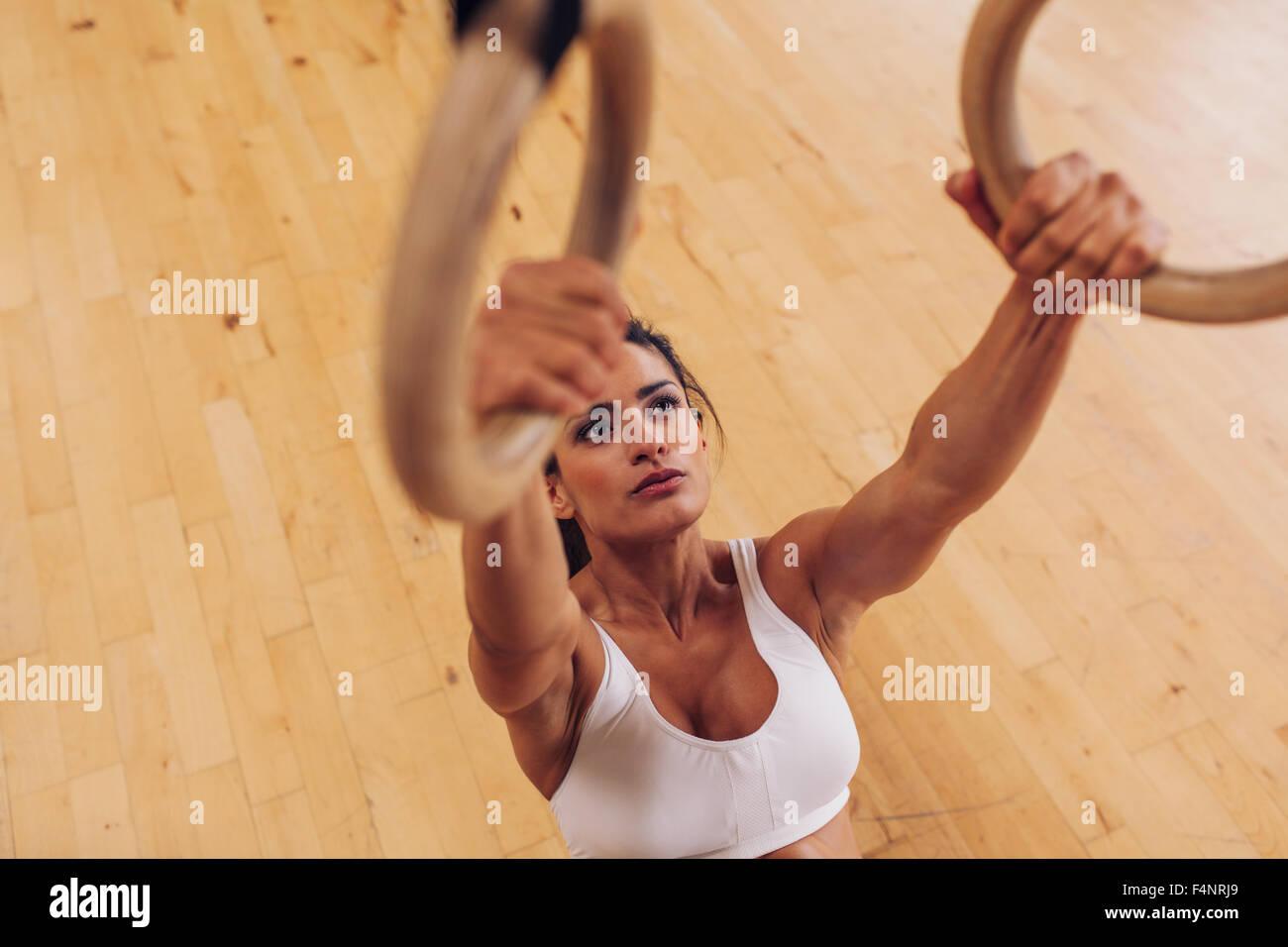 Determinata giovane donna alla palestra. Muscoloso atleta femminile che lavora fuori utilizzando anelli di ginnastica. Immagini Stock