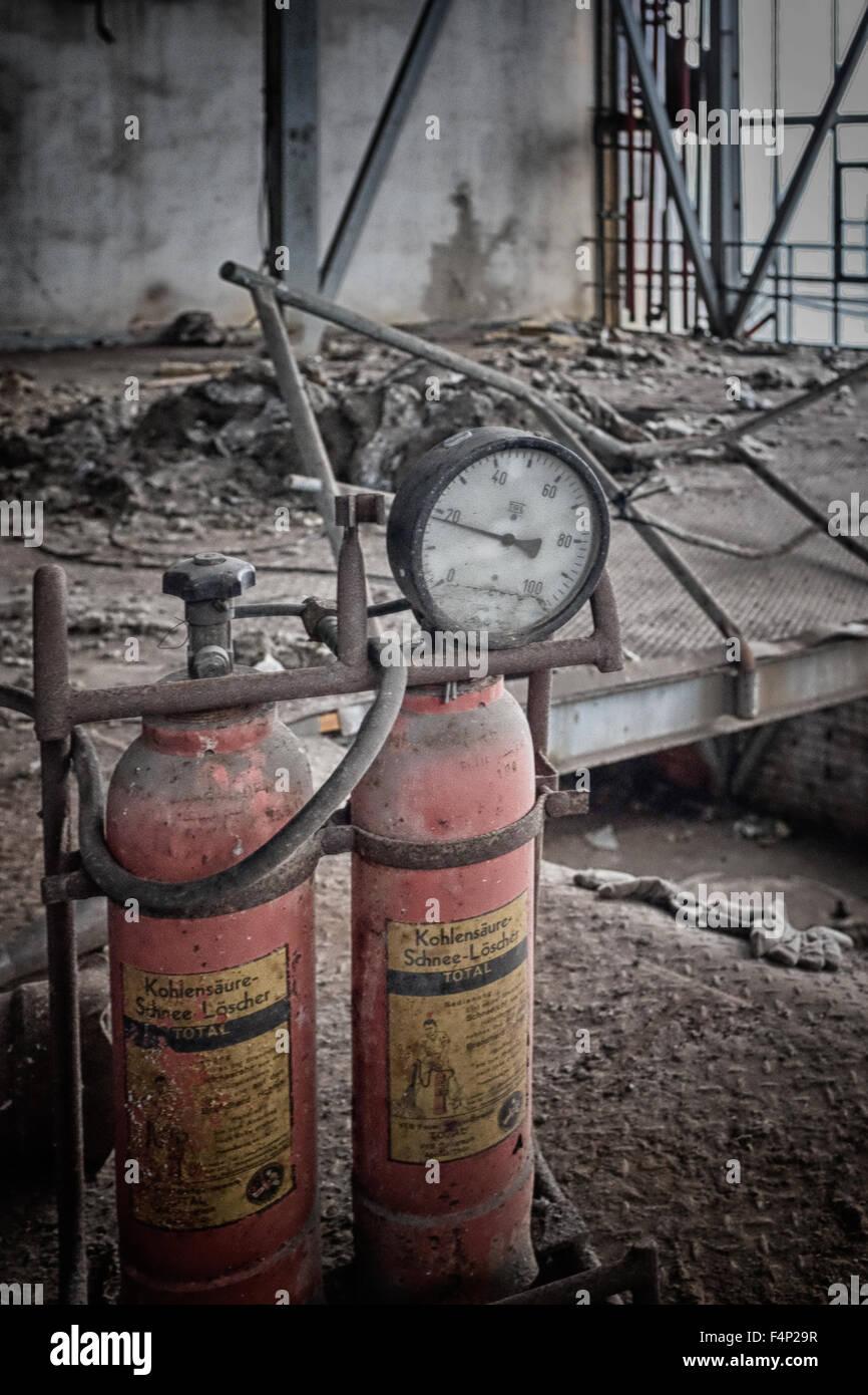 Bottiglie di rosso con un manometro collegato scartato in una fabbrica abbandonata. Foto Stock