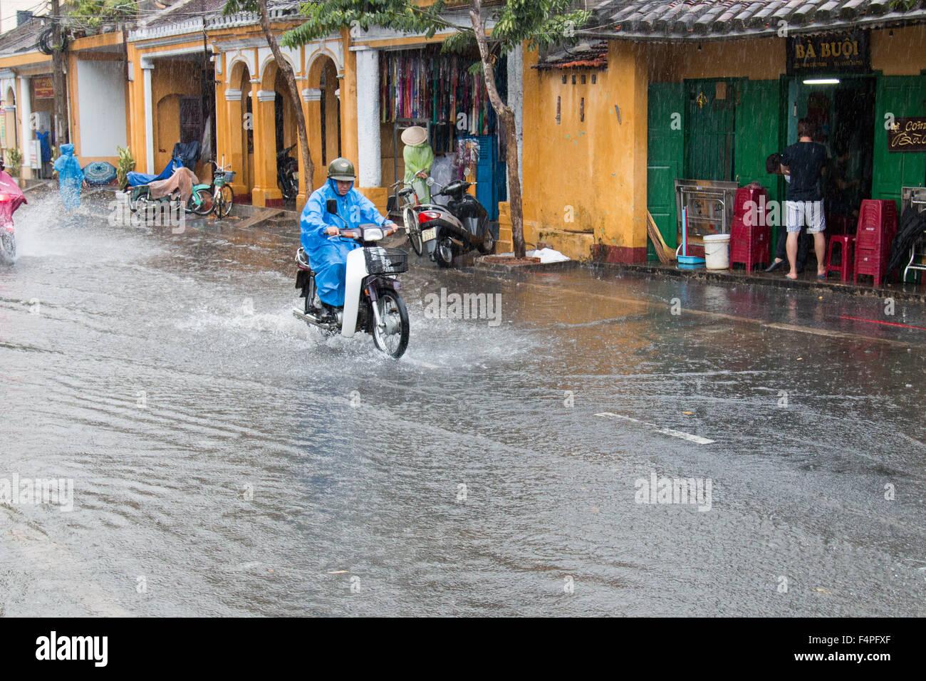 Antica città di Hoi An Vietnam, biker su scooter motociclo attraverso strade allagate durante temporali,Vietnam Immagini Stock