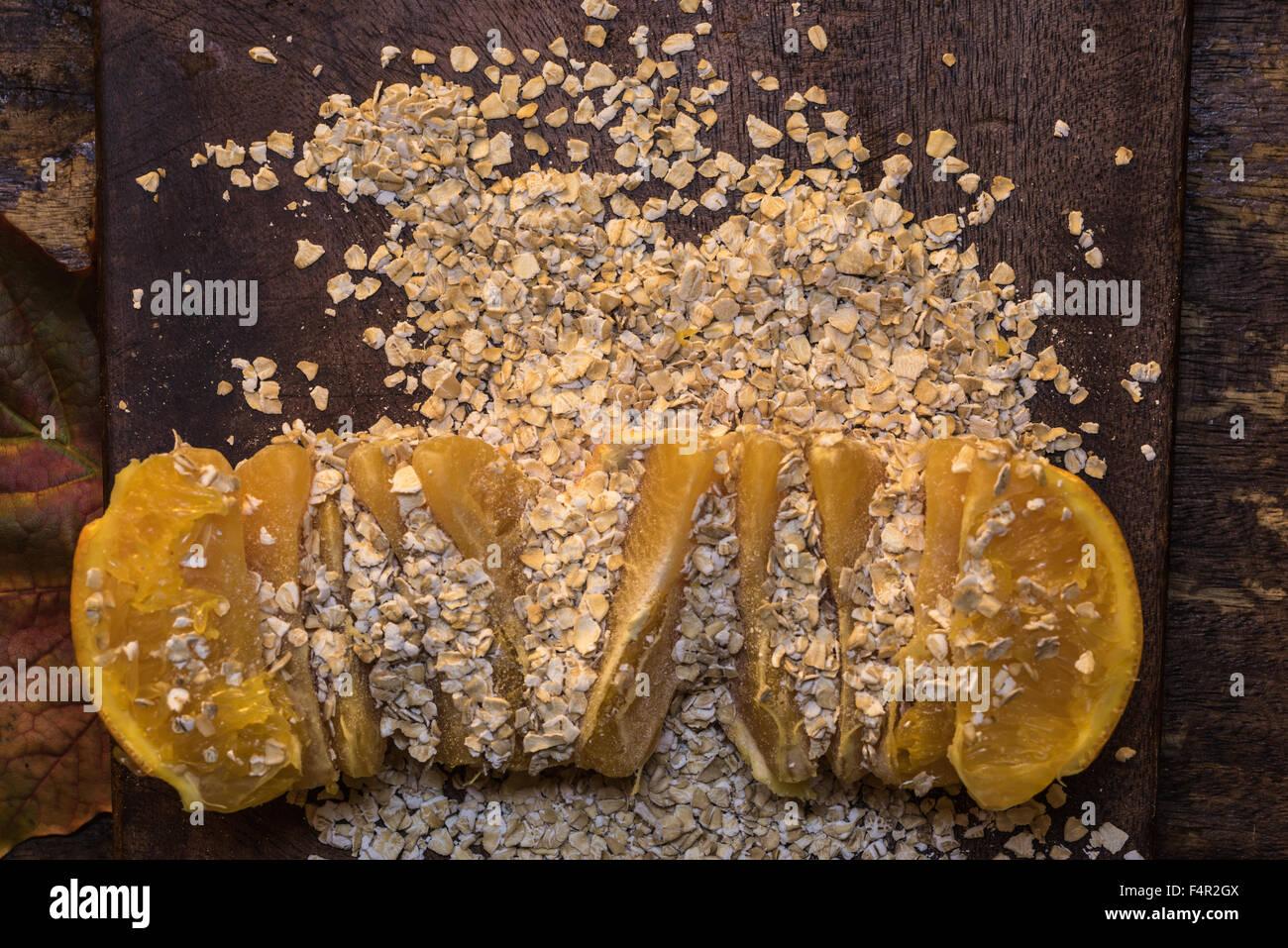I fiocchi d'avena e arancio su un tagliere di legno - Cibo sinergia, cibo sano combinazione Immagini Stock