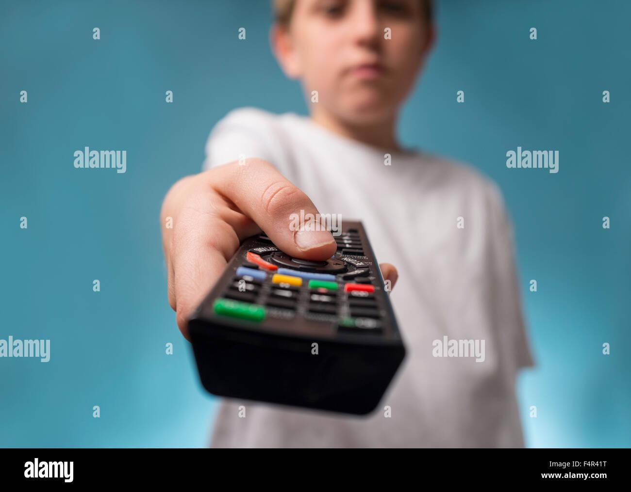 Un annoiato ragazzo cambiando canali utilizzando un telecomando del televisore Immagini Stock
