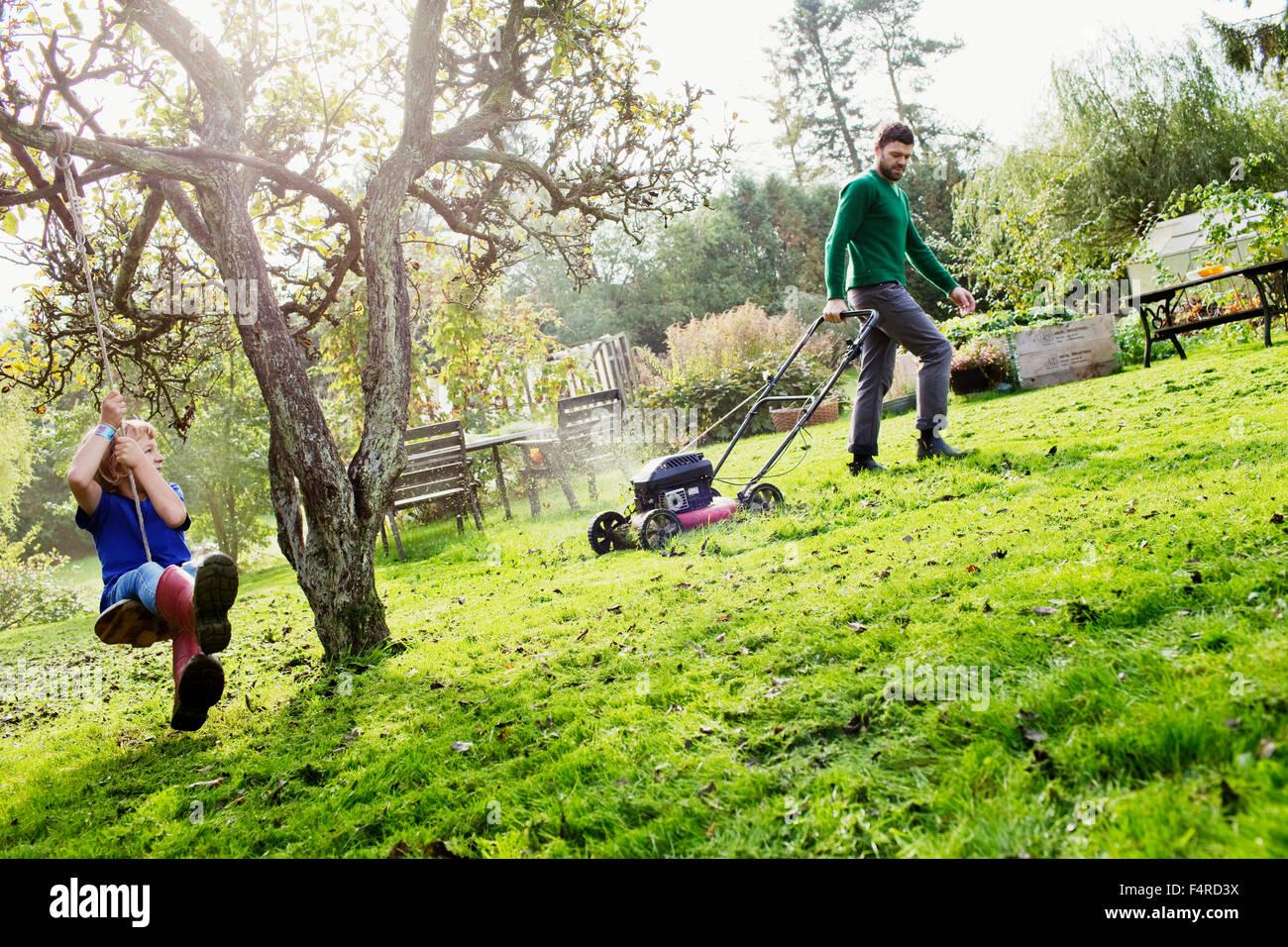 La Svezia, Skane, Osterlen, Borrby, padre e figlio (4-5) nel giardino interno Immagini Stock