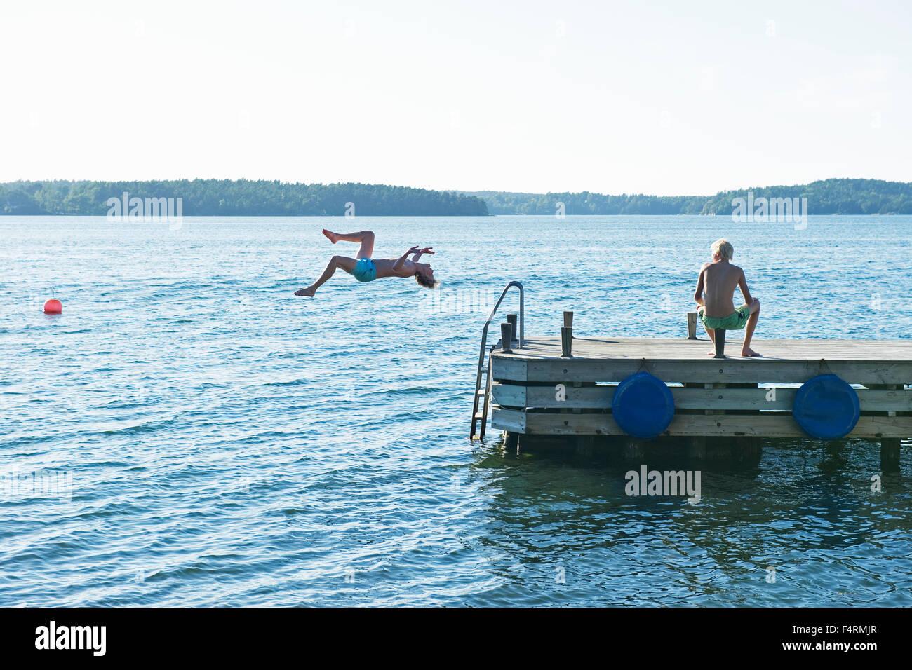 Giovane uomo saltando in acqua dal molo Immagini Stock