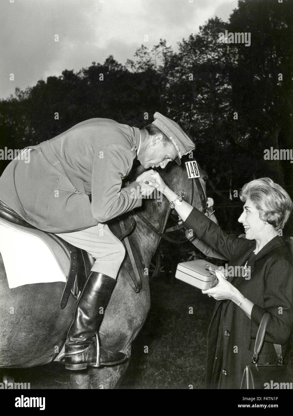 Un poliziotto a cavallo baci la mano di una signora Immagini Stock
