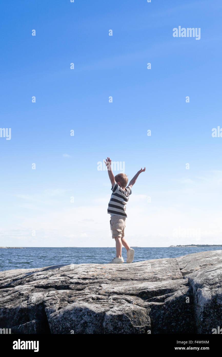 La Svezia, Uppland, Runmaro, Barrskar, ragazzo (6-7) in piedi sul mare e guardando a vista Foto Stock