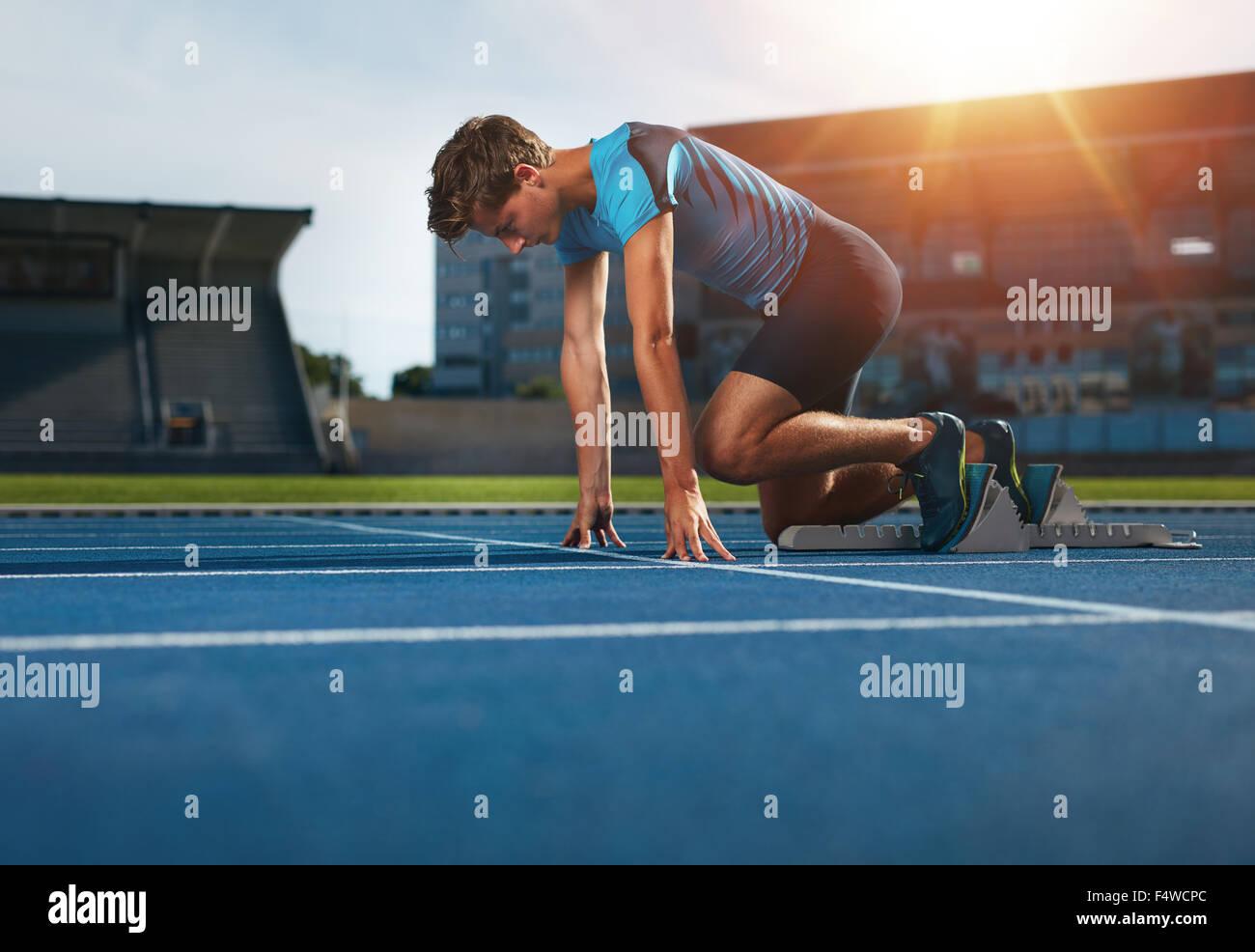 Giovane atleta alla posizione di partenza pronta per iniziare una corsa. Runner maschio pronto per l'esercizio Immagini Stock