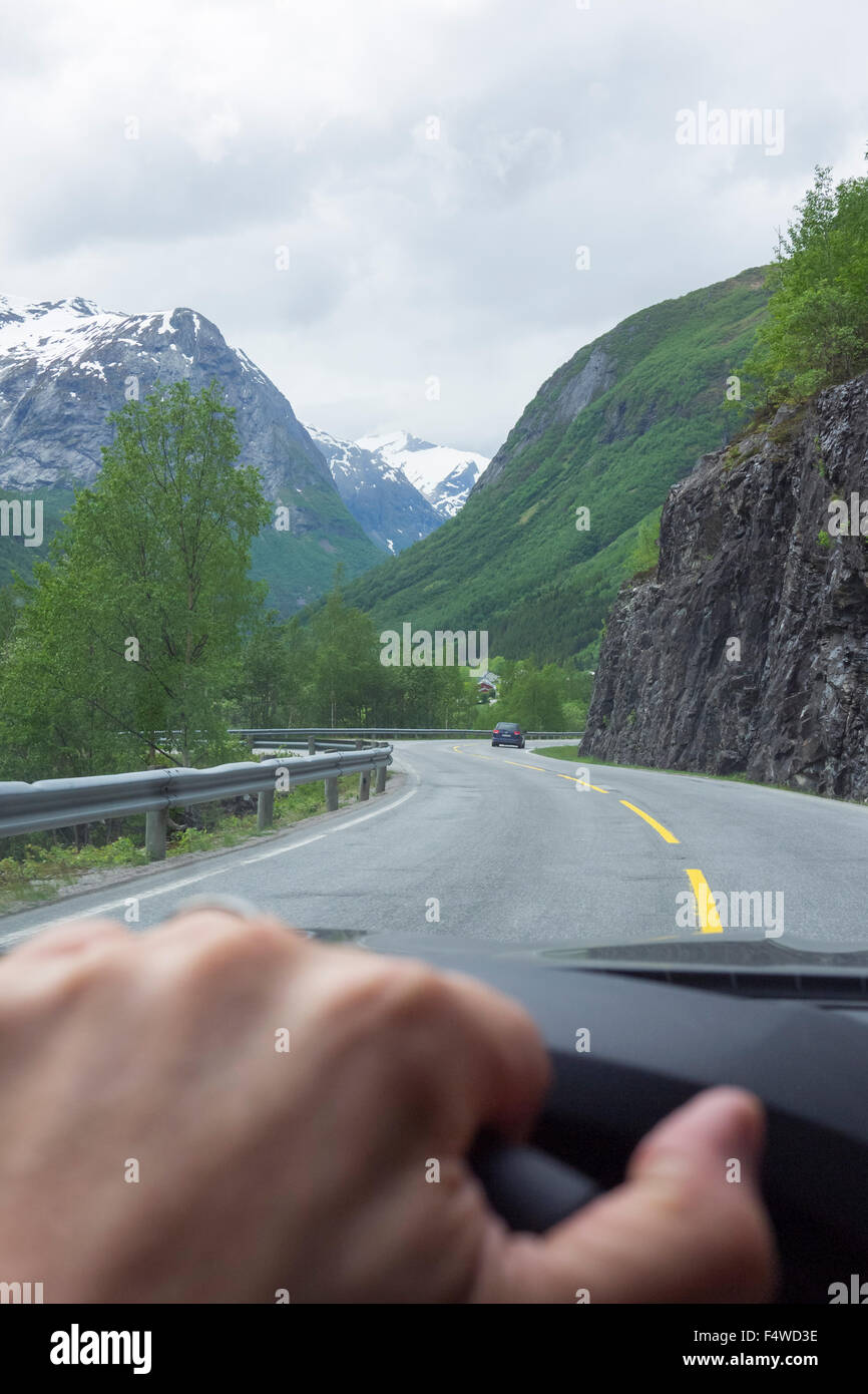 L'uomo la mano sul volante e la gamma della montagna di vedere attraverso il parabrezza Immagini Stock