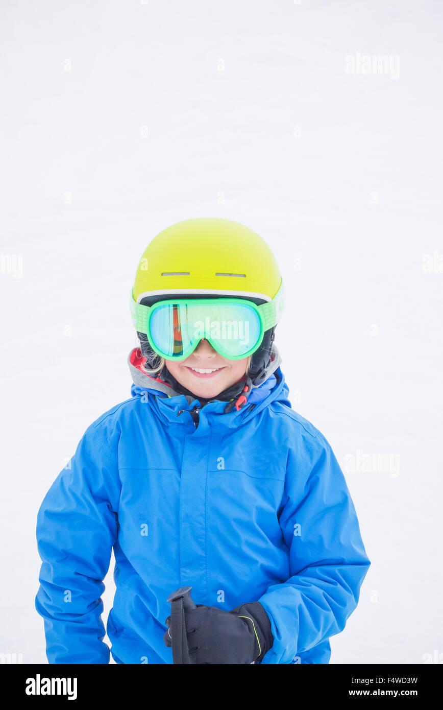 Ragazzo sorridente (10-11) indossare casco e occhiali da sci da neve Immagini Stock