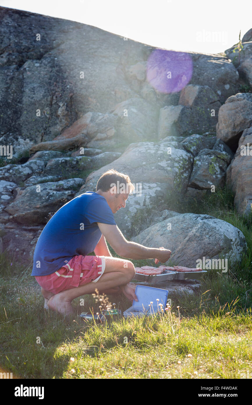La Svezia, Svedese West Coast, Halland, Kungsbackafjorden, uomo di cottura degli alimenti su barbecue grill Immagini Stock