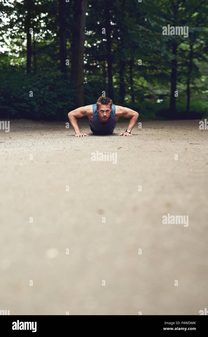 Basso angolo vista di montare un giovane uomo facendo premere-ups in un parco come parte del suo quotidiano esercizio Immagini Stock