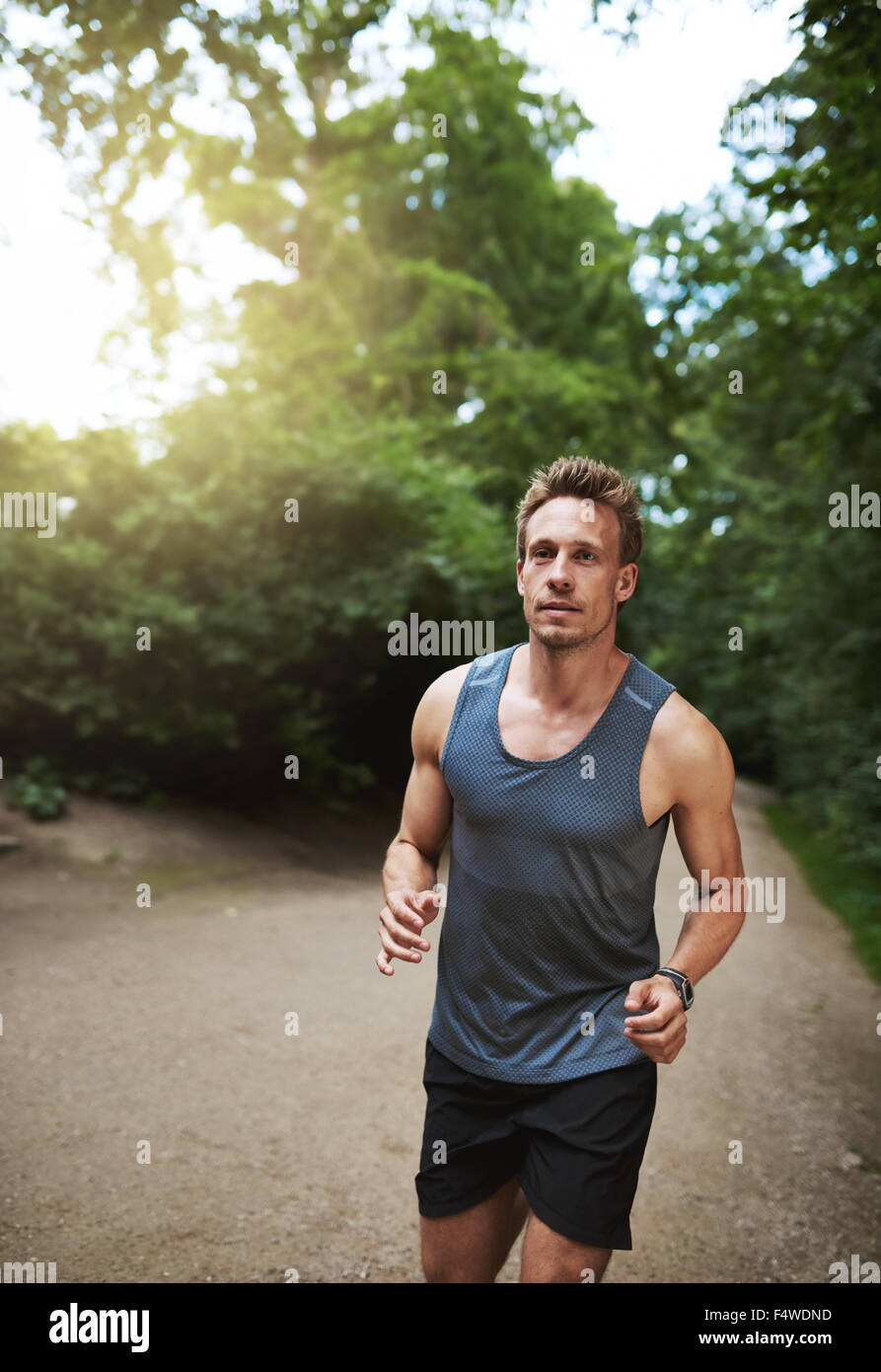 Montare atletico pareggiatore maschio in esecuzione attraverso un parco boscoso verso la telecamera con un aspetto Immagini Stock