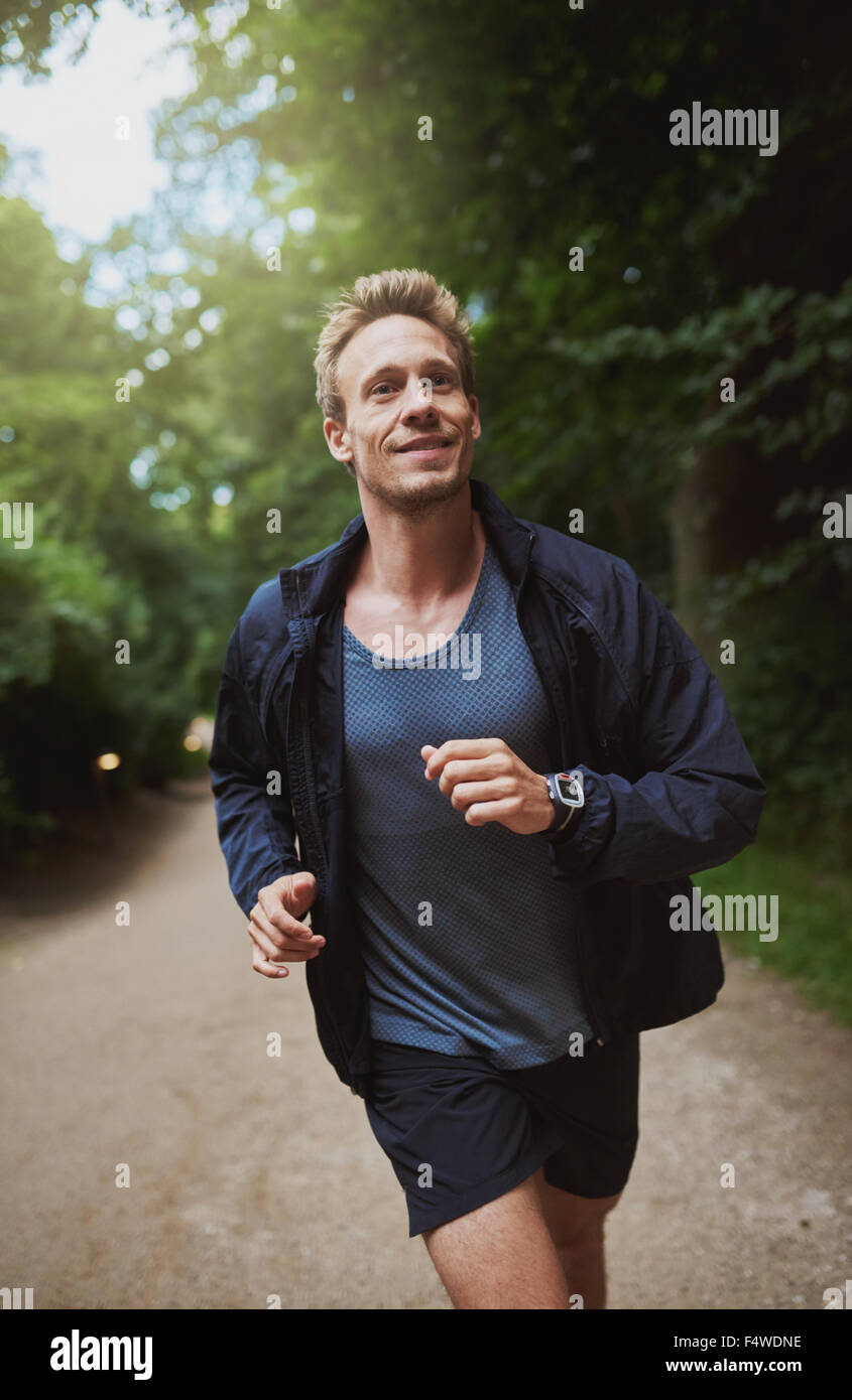 Sano giovane uomo jogging attraverso un parco su una mattina di sole che sta facendo il suo allenamento quotidiano Immagini Stock