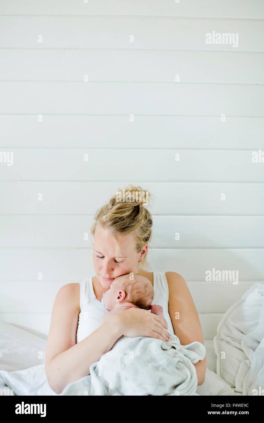 Metà donna adulta holding baby boy (0-1 mesi) nelle sue braccia Immagini Stock
