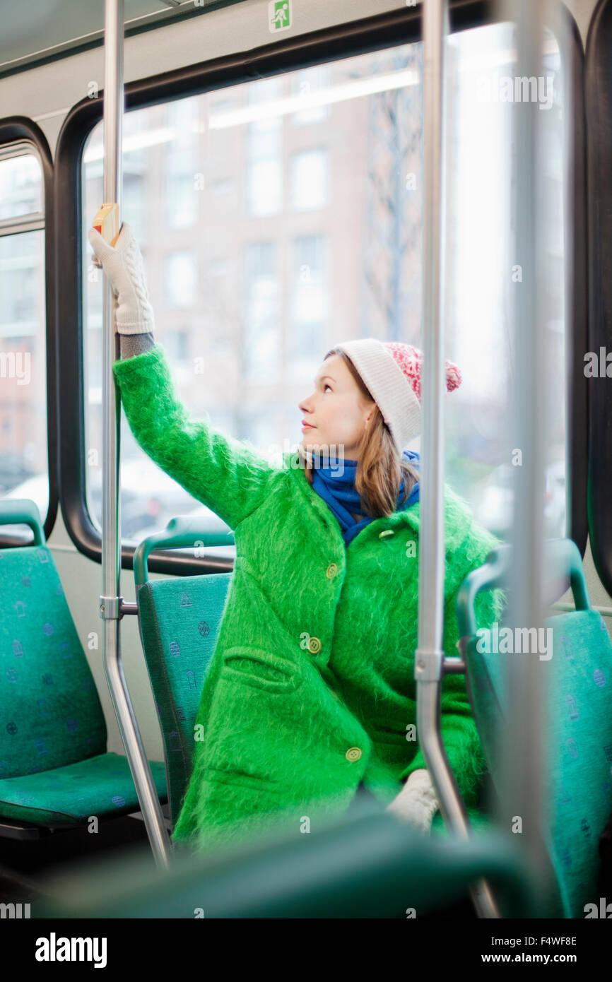 Giovane donna richiesta premendo il pulsante di arresto in tram Immagini Stock