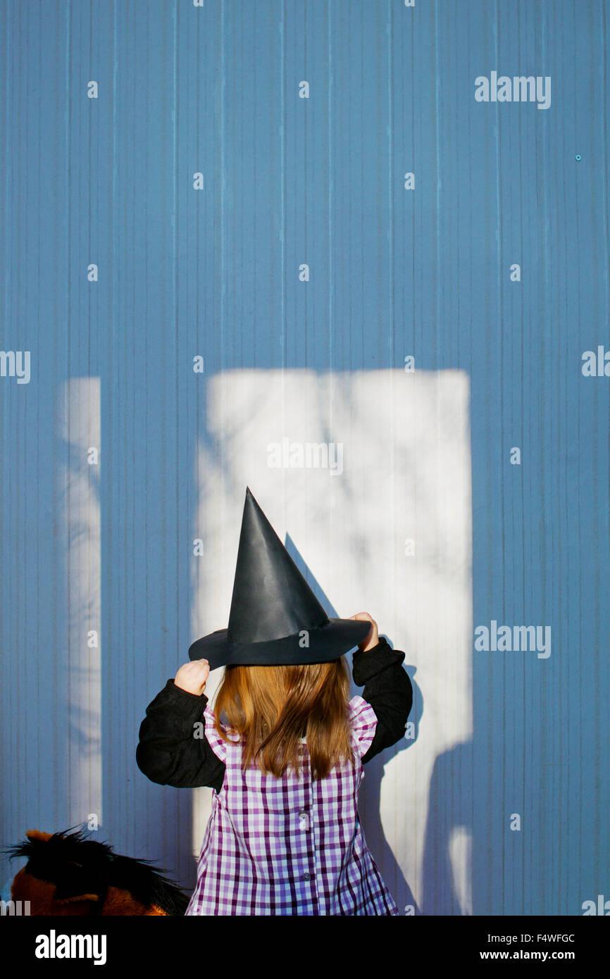 La ragazza (4-5) indossando il costume di strega a Eastertime Immagini Stock