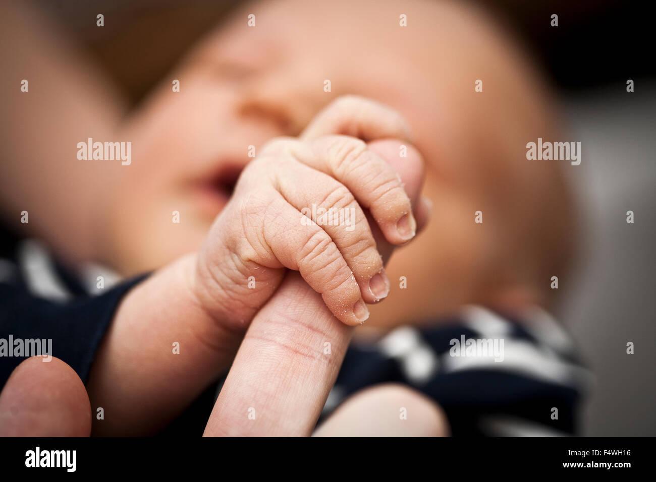 Ragazzo (0-1 mesi) tenendo il padre del dito Immagini Stock