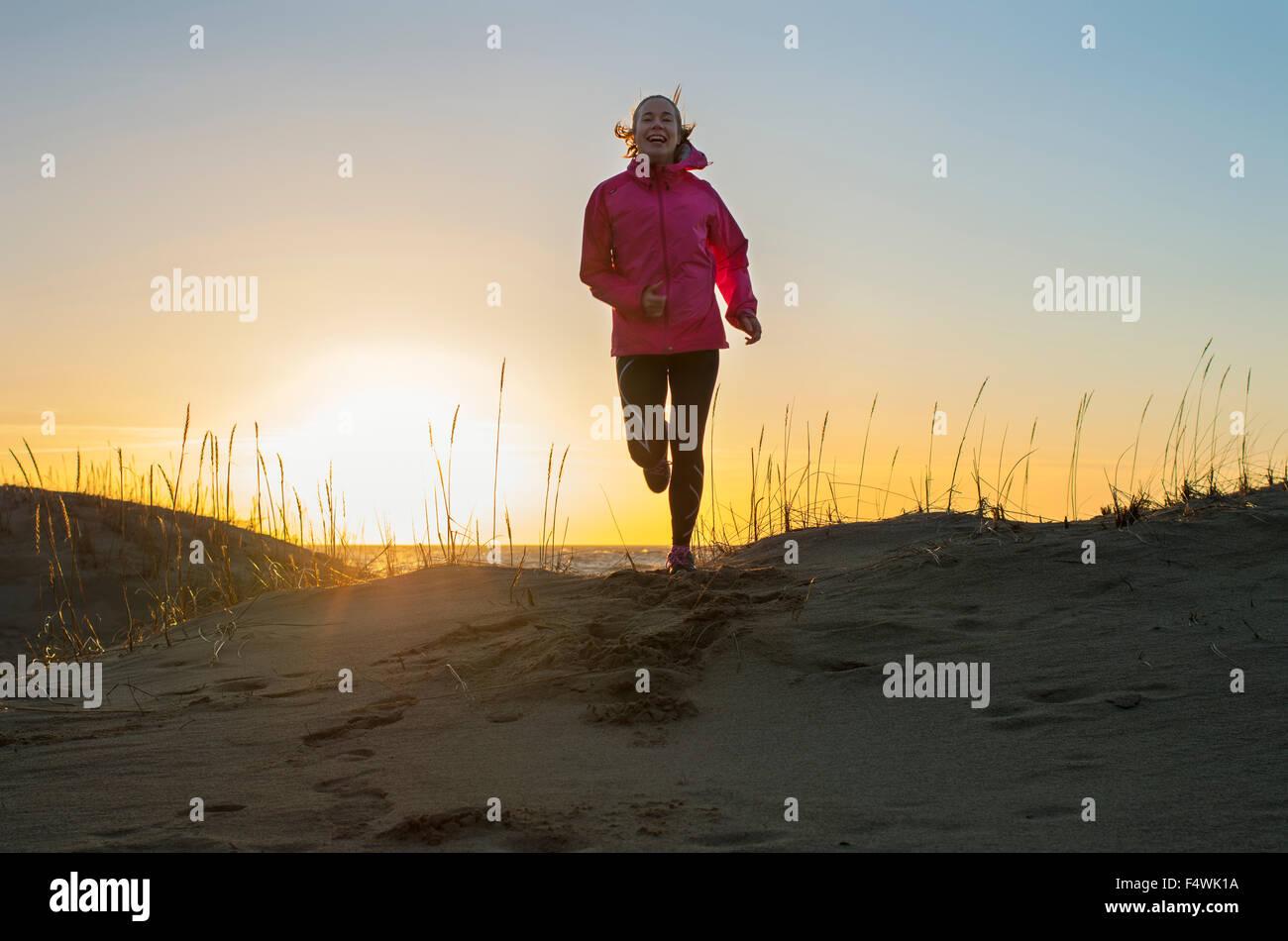 Finlandia, Pohjanmaa, Pietarsaari, Faboda, giovane donna jogging sulla spiaggia al tramonto Immagini Stock