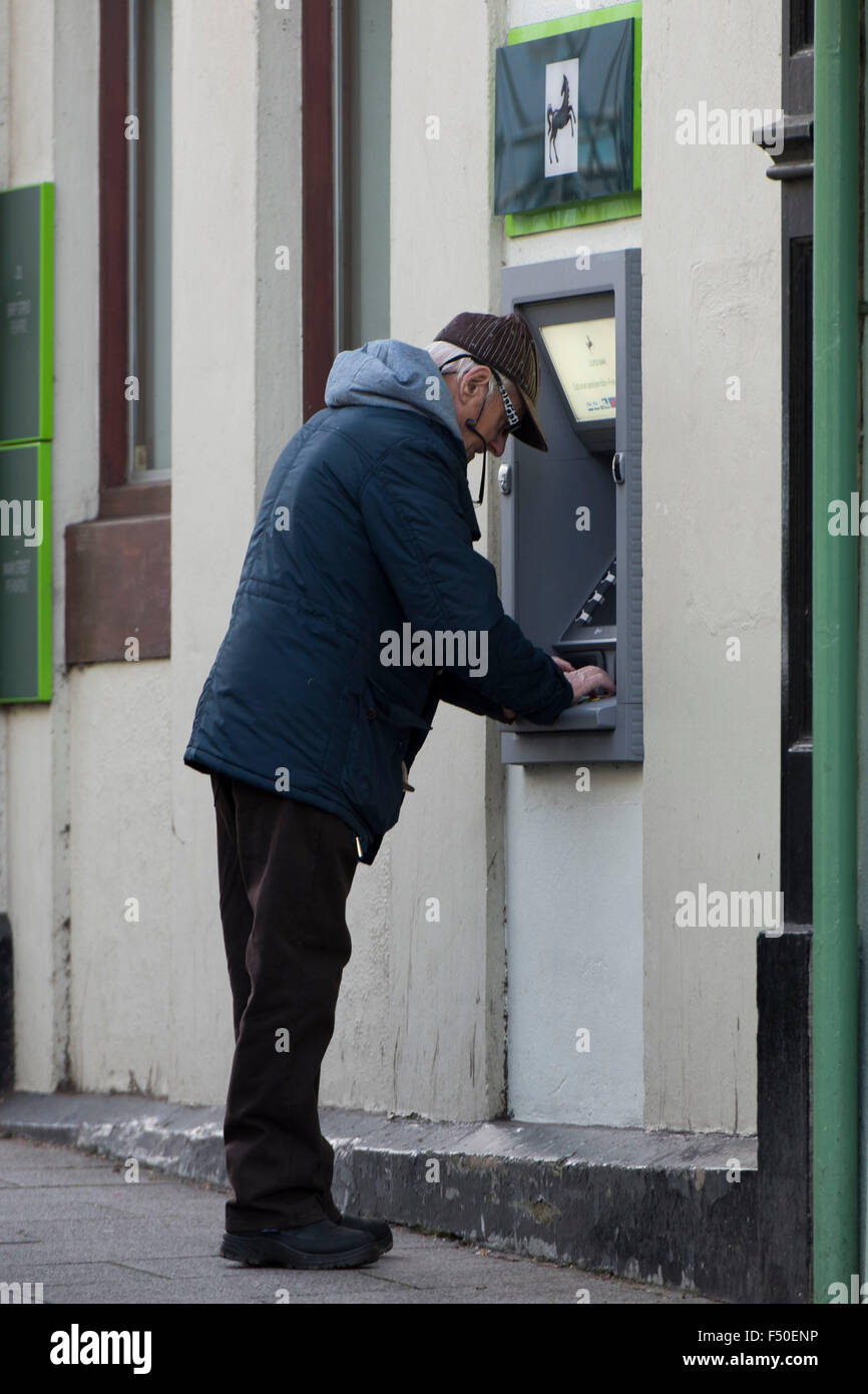 Un pensionato OAP ritira incassare utilizza un Lloyds Bank bancomat. Foto Stock