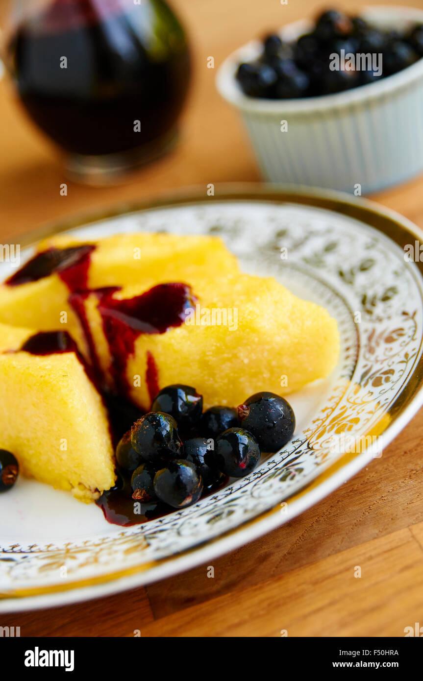 Fritti polenta di farina di mais con sciroppo di ribes nero Immagini Stock