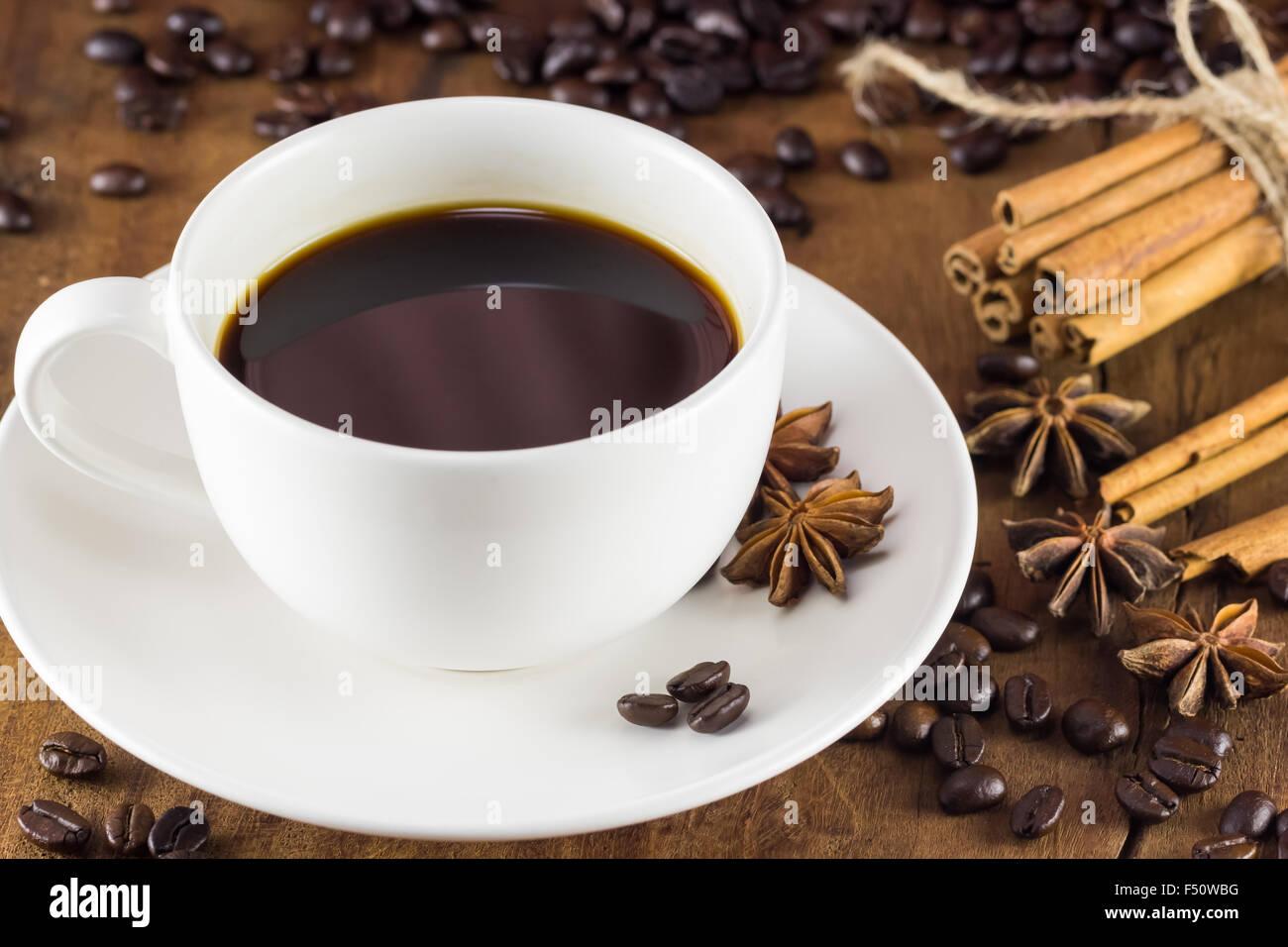 Caffè in tazza con i chicchi di caffè e bastoncini di cannella su uno sfondo di legno , caldo tonificante, Immagini Stock