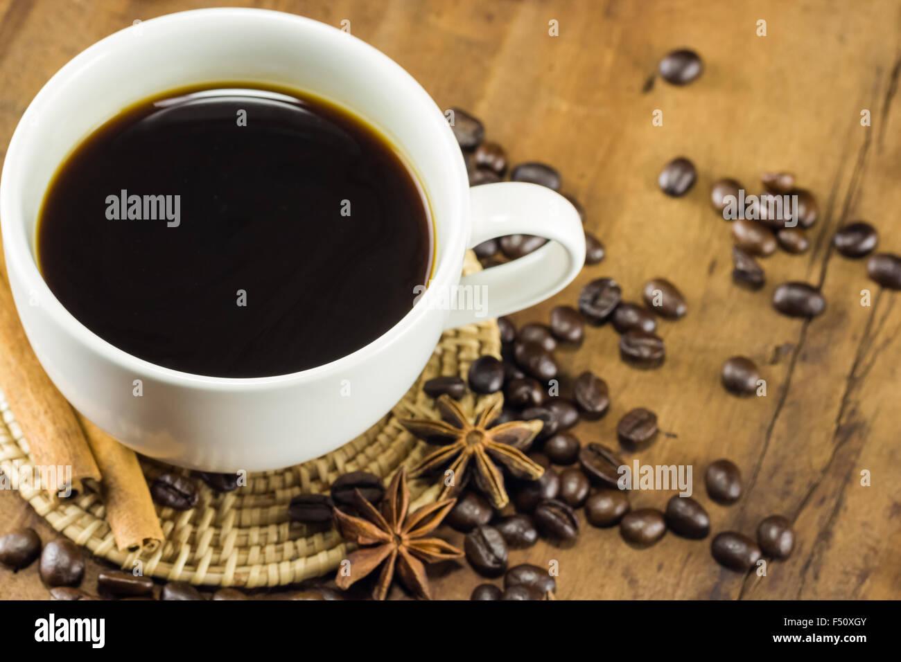 Caffè in tazza con i chicchi di caffè e bastoncini di cannella su uno sfondo di legno caldo, tonificazione, Immagini Stock