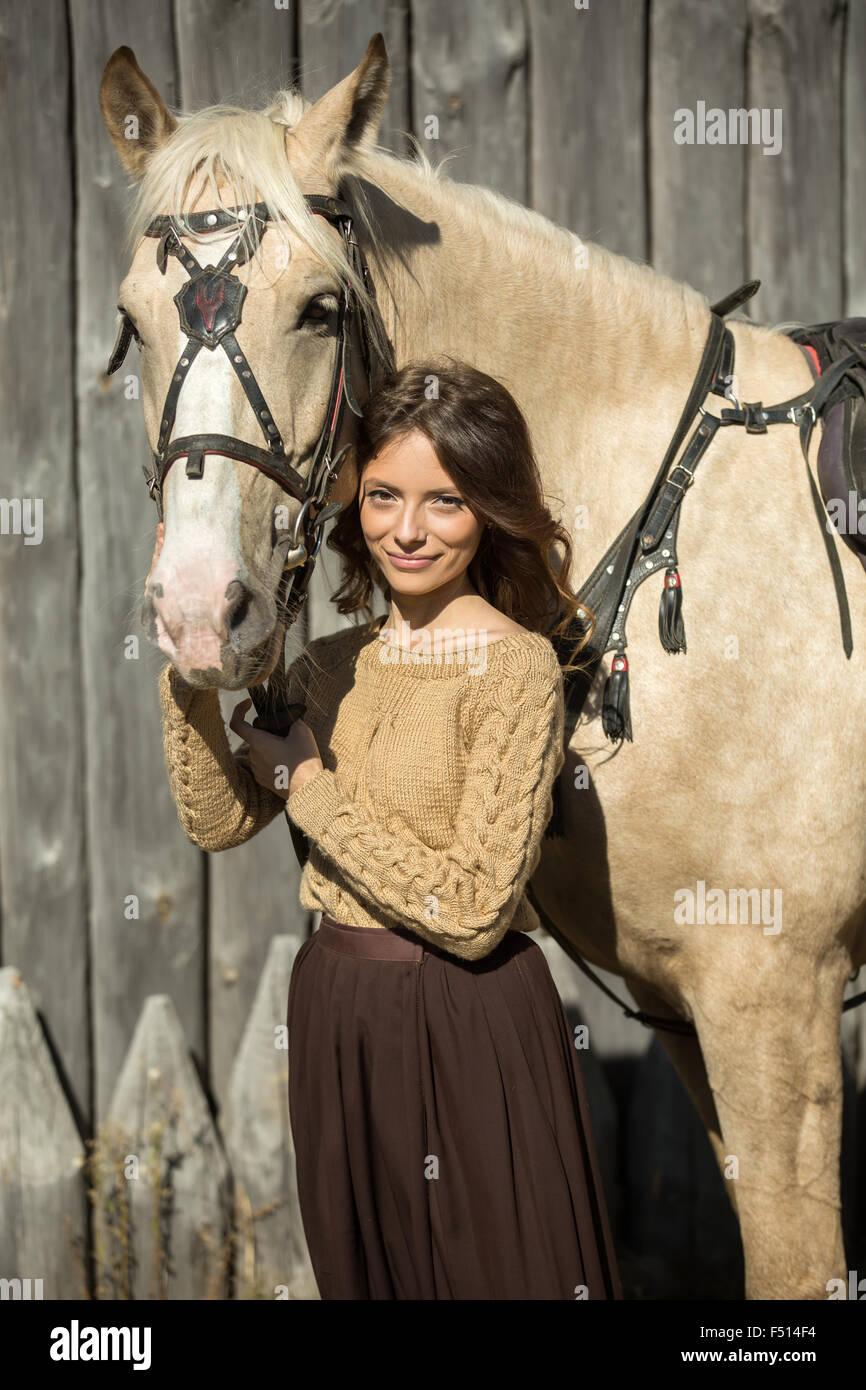 Giovane ragazza attraente è il camminare con il suo cavallo Foto Stock