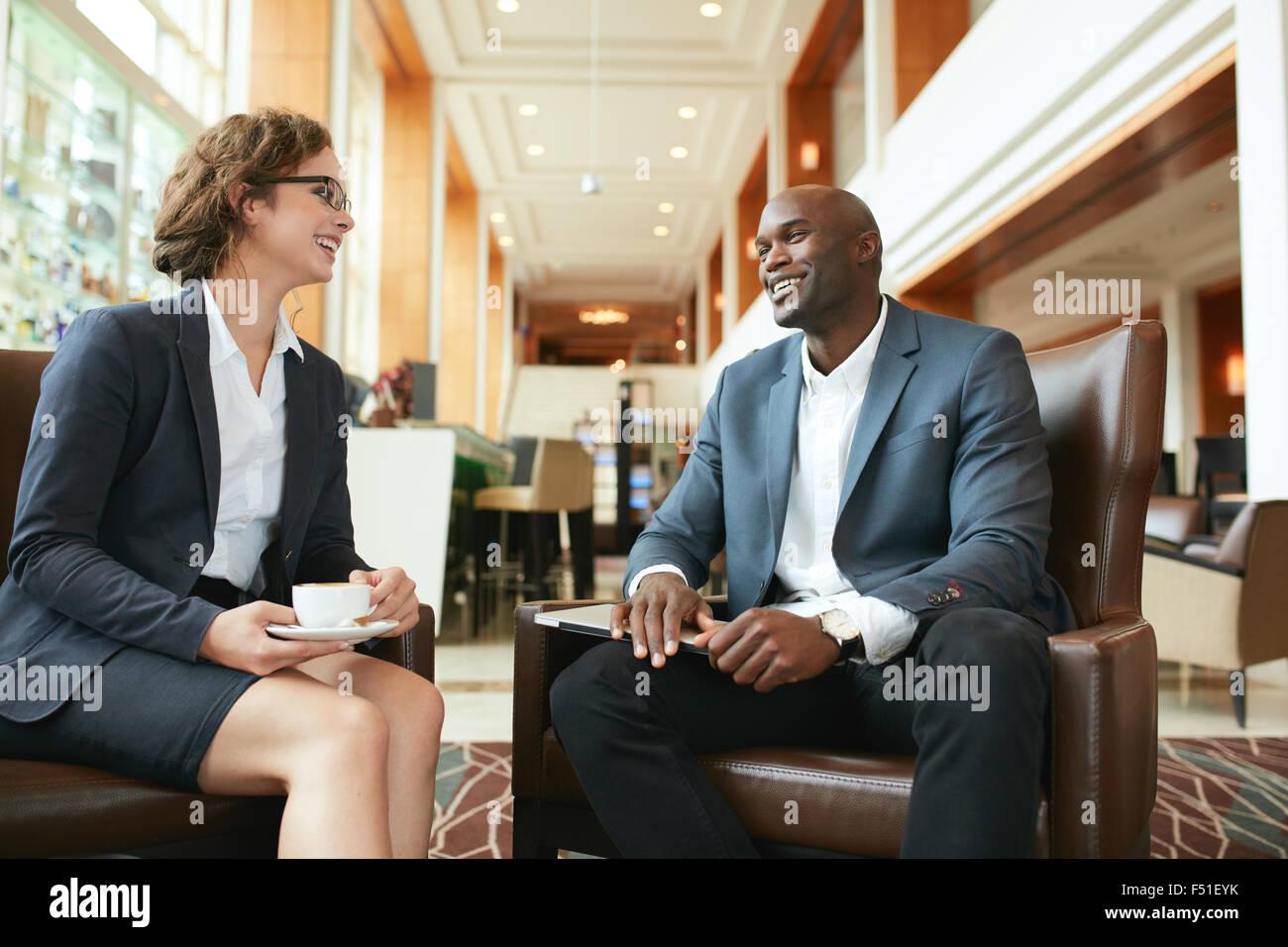 Ritratto di felice giovane imprenditrice in riunione con business partner presso la lobby dell'hotel. La gente Immagini Stock