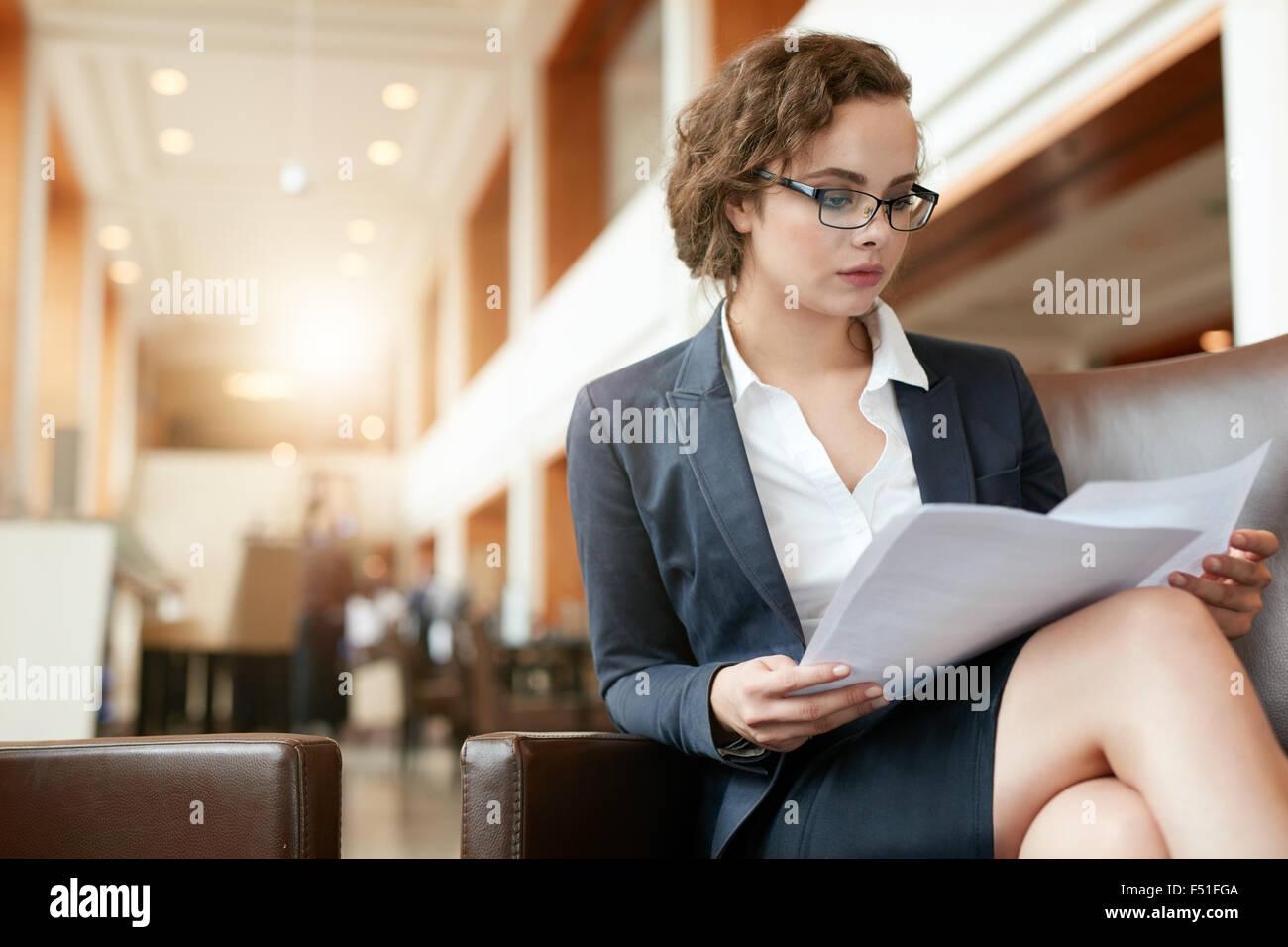 Ritratto di imprenditrice lettura documento. Professionale femminile in hotel lobby esaminando le carte. Immagini Stock