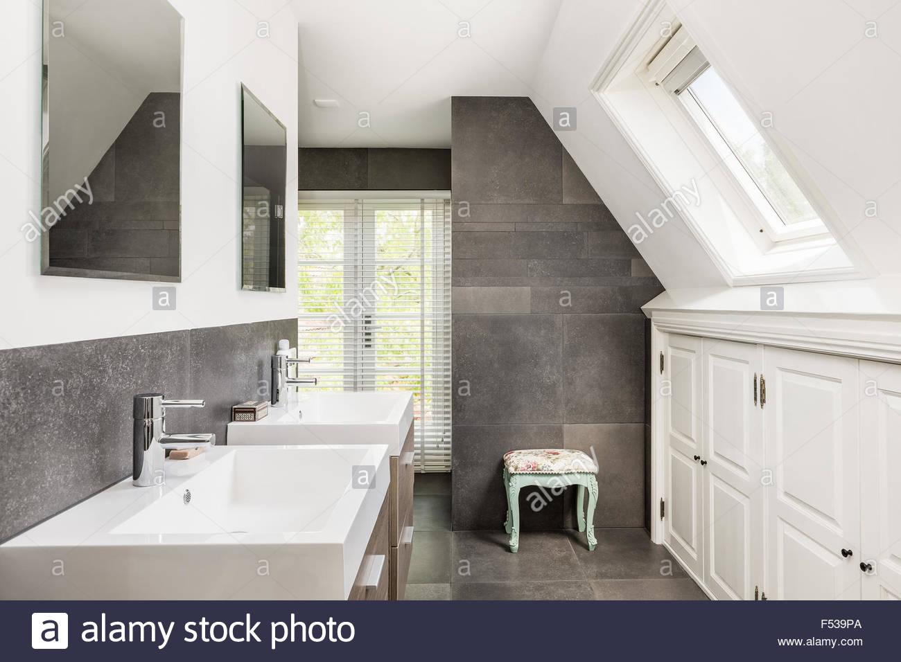 Piccolo e moderno bagno con doppio lavabo e piastrelle scure foto