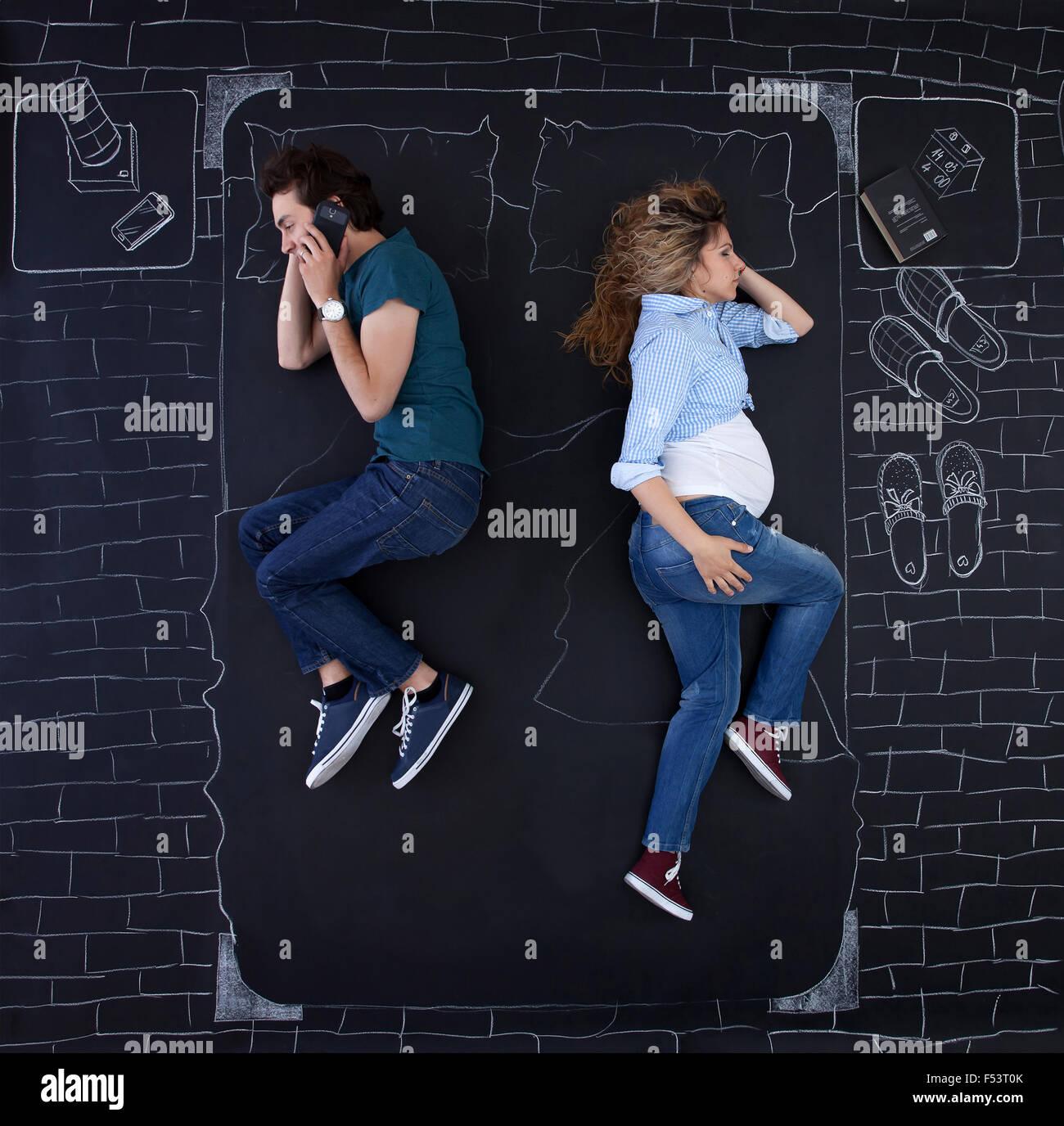 Coppia giovane delle attività in letto. L'uomo sta parlando al telefono mentre lei sta dormendo. Immagini Stock