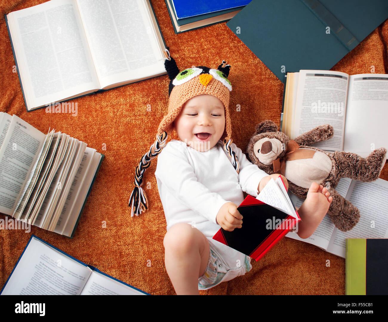 Un anno di età del bambino libri di lettura con Teddy bear Immagini Stock
