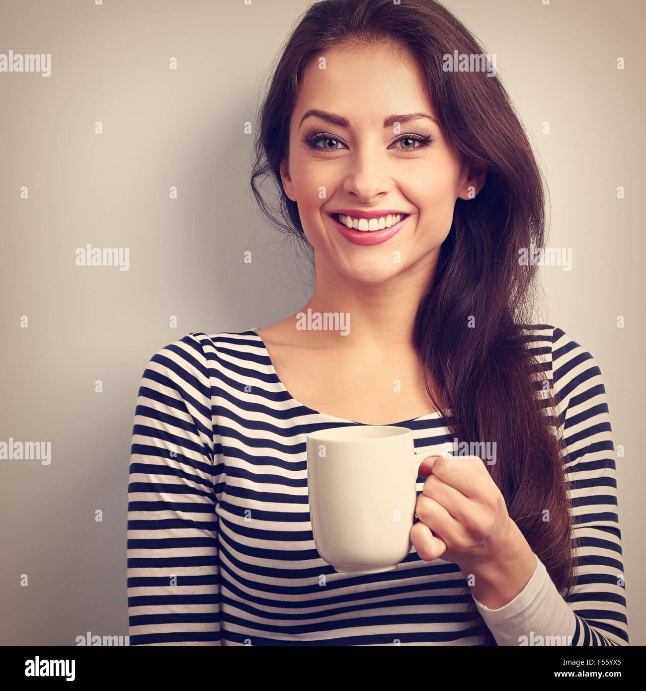 Felice toothy sorridente casual donna giovane con tazza di tè. Vintage closeup ritratto Immagini Stock